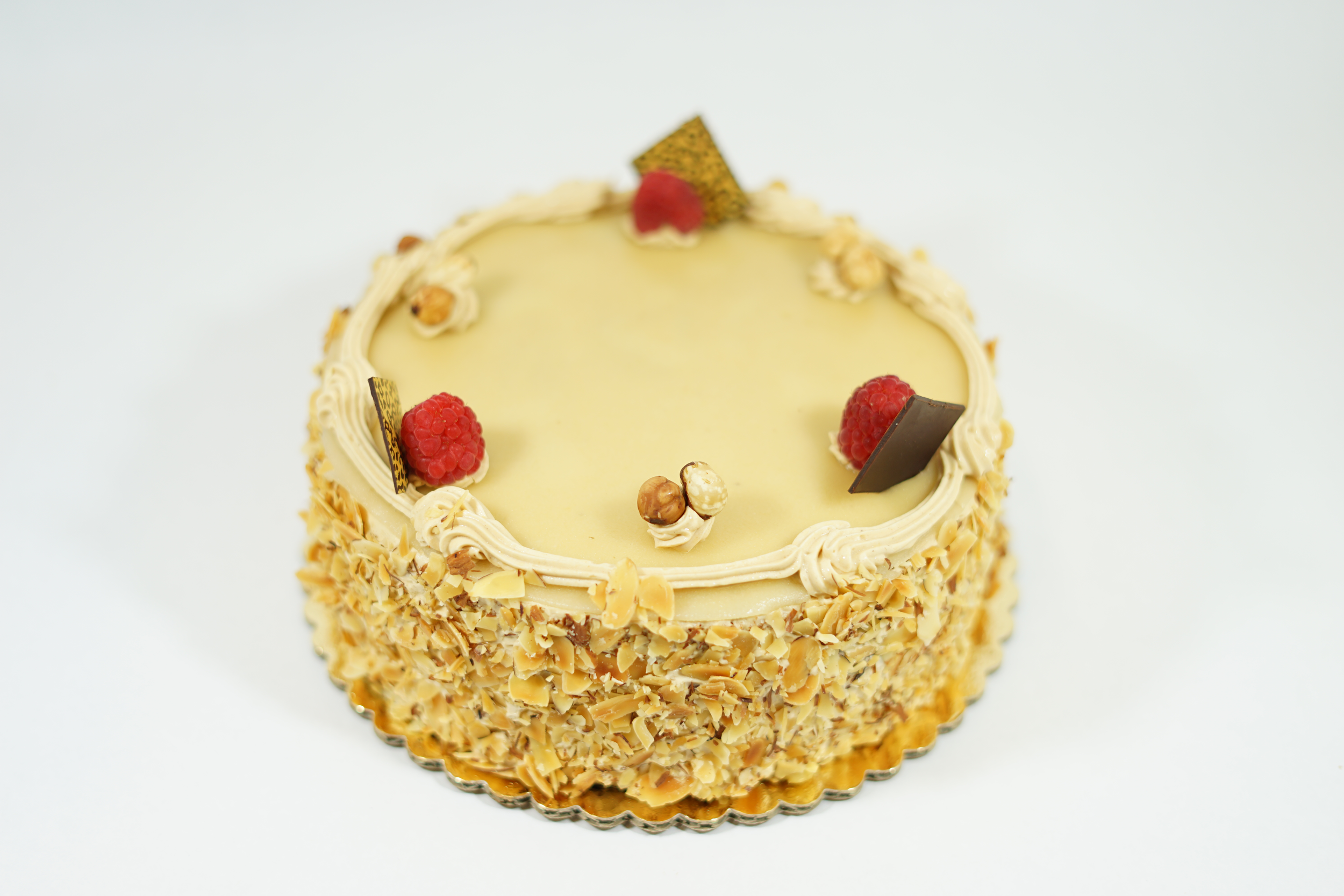 Hazelnut - Genoise sponge cake with cognac syrup, hazelnut chocolate mousse, and almond paste filling. Iced with a hazelnut buttercream and decorated with almond slivers on the side.