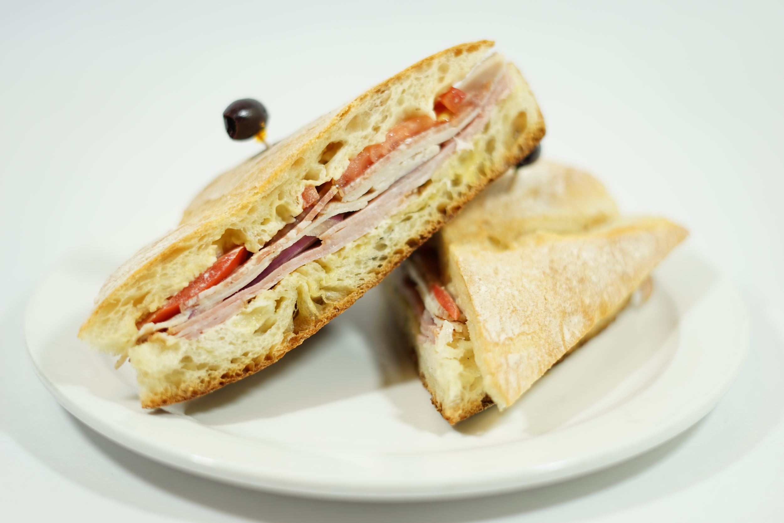 Monte Carlo - On Provencal bread with Dijon mayo spread, sliced tomatoes, onions, turkey, ham, salami, and drizzled with Dijon vinaigrette dressing.