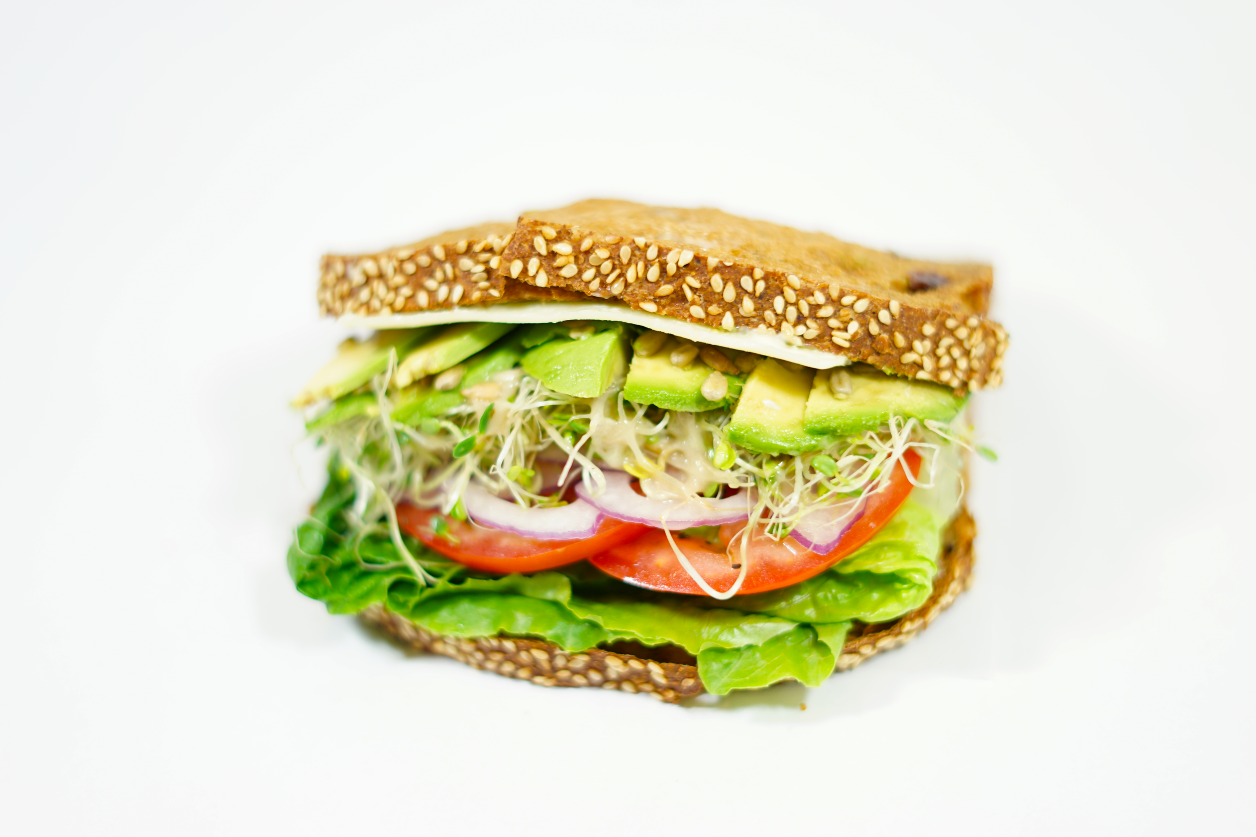 Vegetarian - On our 3 seed bread, also known as Raisin Walnut, with mayo, sliced avocado, sunflower seeds, swiss cheese, lettuce, sliced tomatoes and onions, sprouts, drizzled with dijon vinagrette dressing, and sprinkle of salt and pepper.