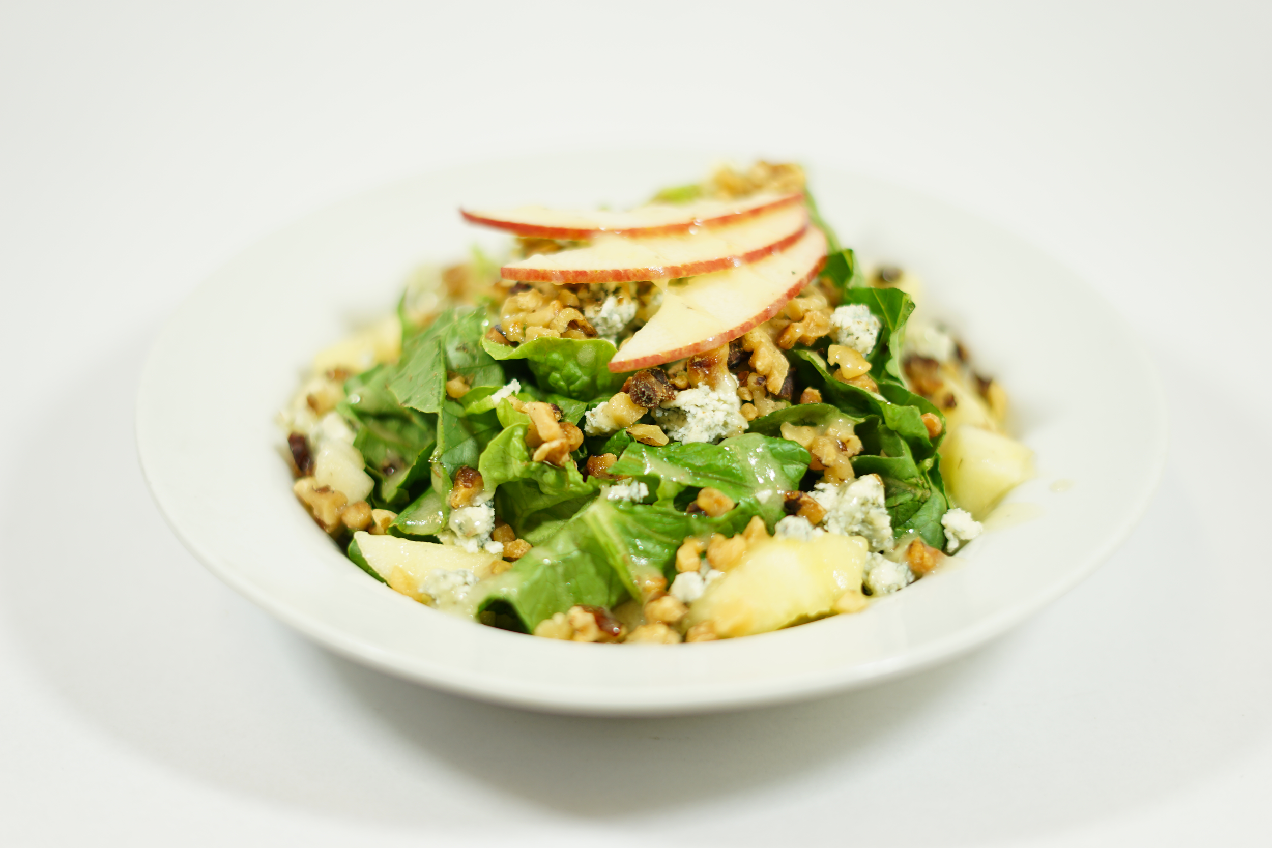 Apple Walnut - Apple vinaigrette dressing tossed with a bed of romaine lettuce, topped with chopped Fuji apples, crumbled bleu cheese, and roasted walnuts.