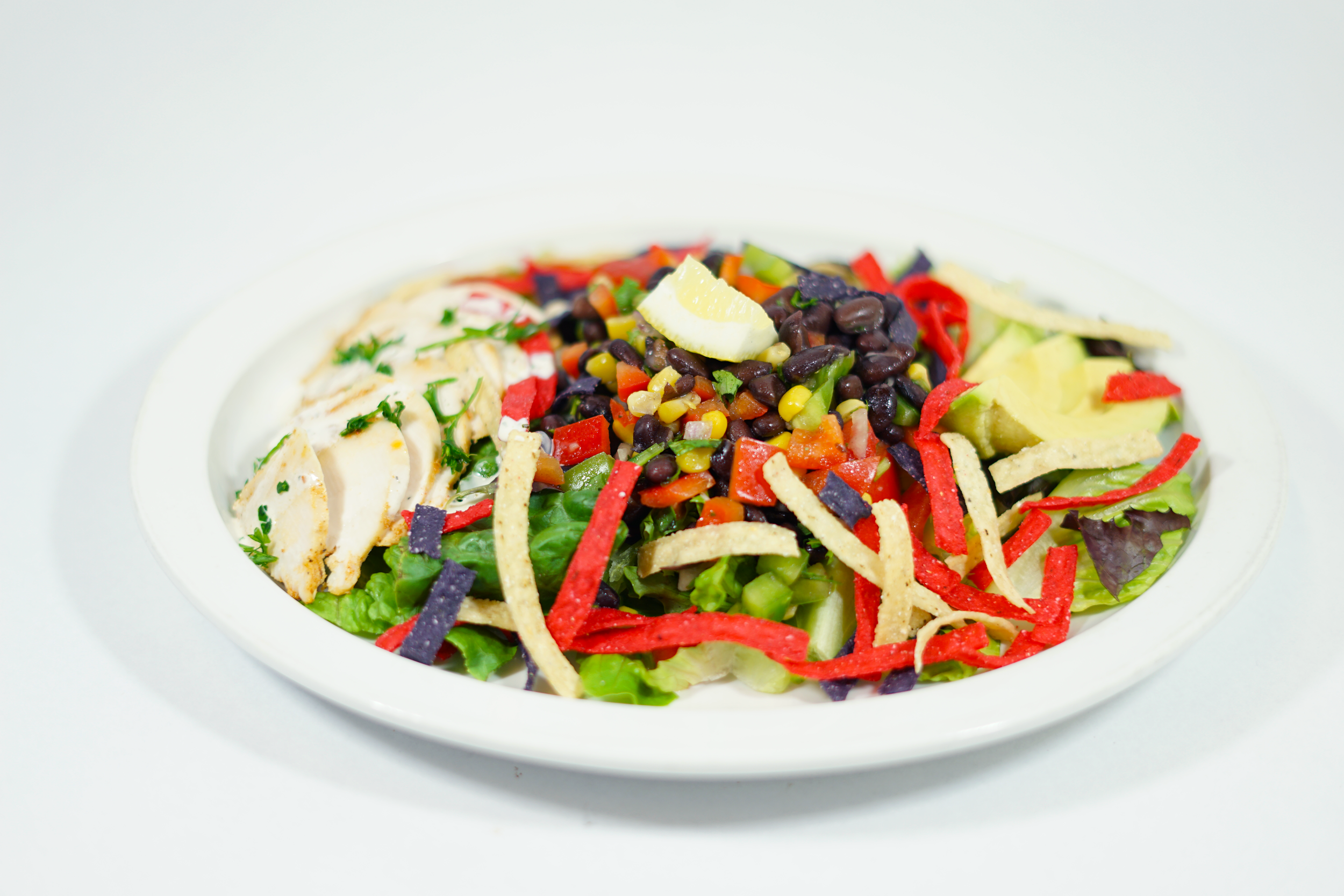 Summer:Southwestern Chipotle Chicken - A black bean, red onion, bell pepper, corn and cilantro mix over a bed of mixed greens with sliced chicken breasts, avocado, and tri color tortilla chips. Served with homemade chipotle ranch dressing.