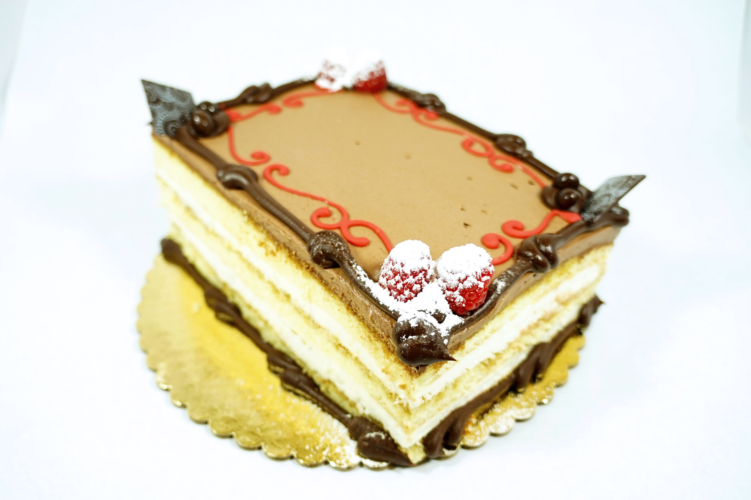Tiramisu - Genoise cake with rum syrup, tiramisu syrup and mascopone cream cheese filling. Topped with chocolate whipped cream.