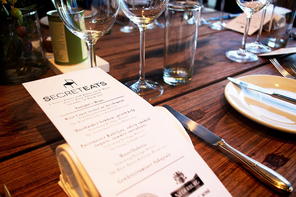 A SecretEATS dinner menu sits on a dark wood table alongside flatware and glasses.