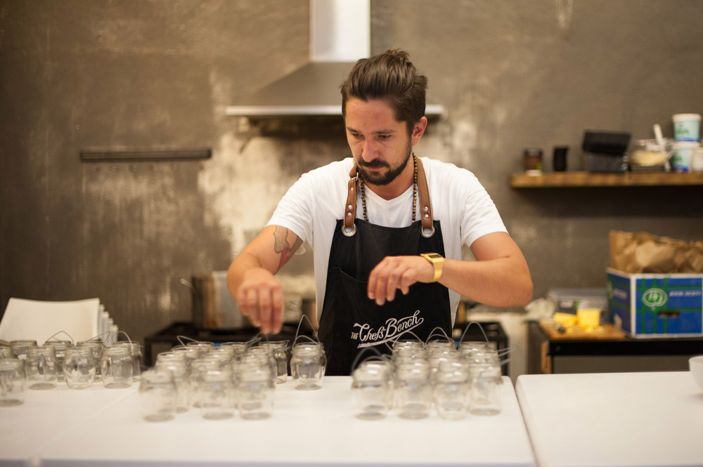 A chef wearing a black apron carefully prepares dozens of jars in preparation for a SecretEATS underground dinner.