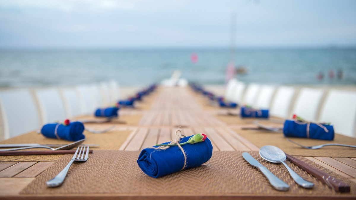 Blue napkins are perfectly rolled on a long table, waiting for a SecretEATS brunch by the ocean.