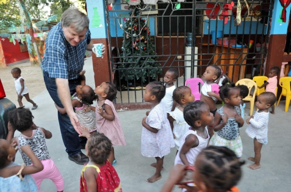 A tidal wave of toddlers surrounds John.