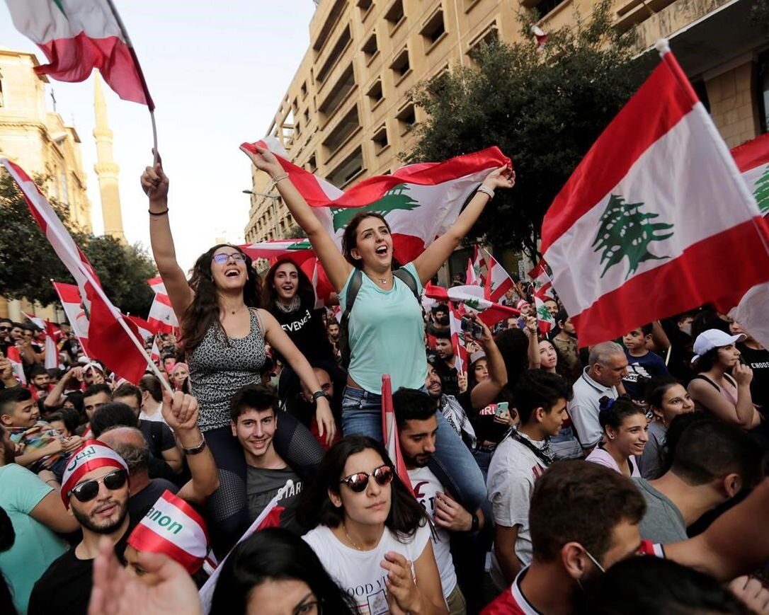 Photo Credit: Anti-government protesters shout slogans in Beirut, Lebanon, Sunday, Oct. 20, 2019. Tens of thousands of Lebanese protesters of all ages gathered Sunday in major cities and towns nationwide, with each hour bringing hundreds more people to the streets for the largest anti-government protests yet in four days of demonstrations.    HASSAN AMMAR / AP PHOTO