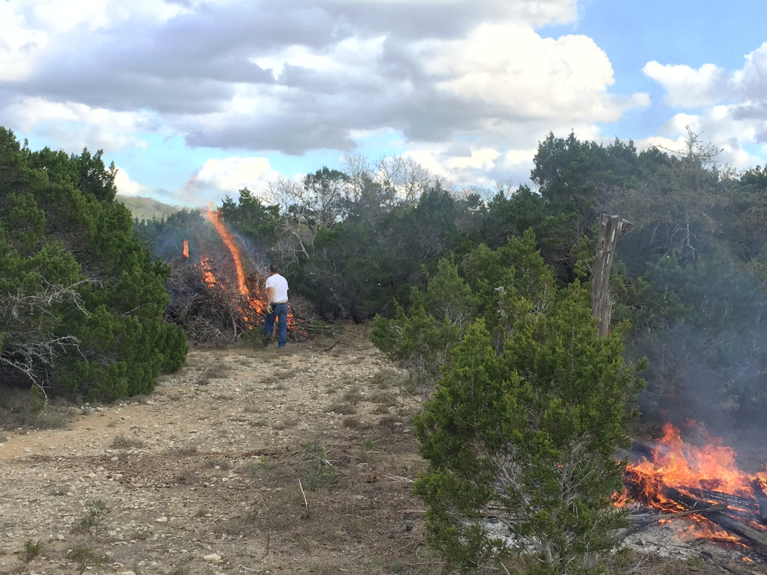 One of many burn days  THE BARN WILL EVENTUALLY GO ON THE RIGHT, WITH WITH HOUSE AND CARPORT IN FRONT OF JOE ON THE LEFT