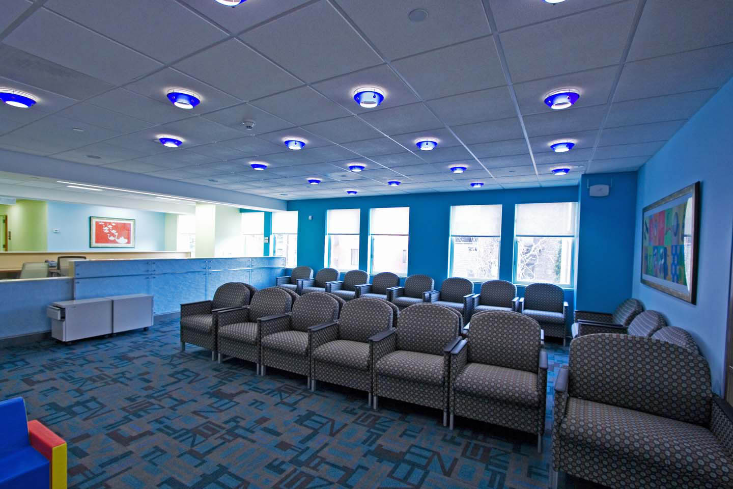 "Color, color was our primary tool in this pediatrics waiting room. The use of blue was meant to grab the positive attention of the children while also creating an over all calming space.  The several blue shades found in the alphabet carpet, the glass housing around the down-lights and the reflective patterned surface of the reception desk fostered a ""blue"" space that felt more like a playroom rather than an waiting room."