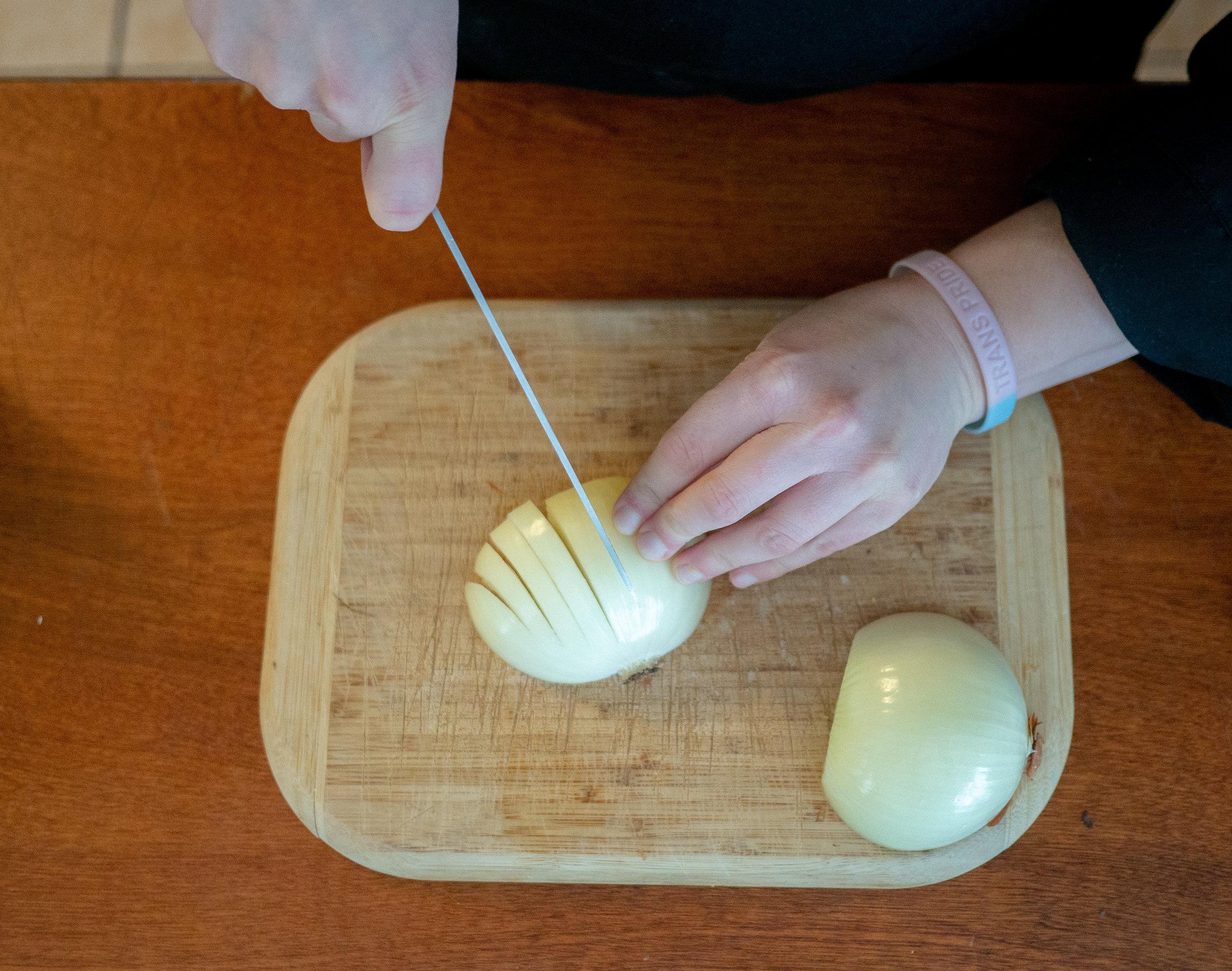 someone cutting an onion on a cutting board