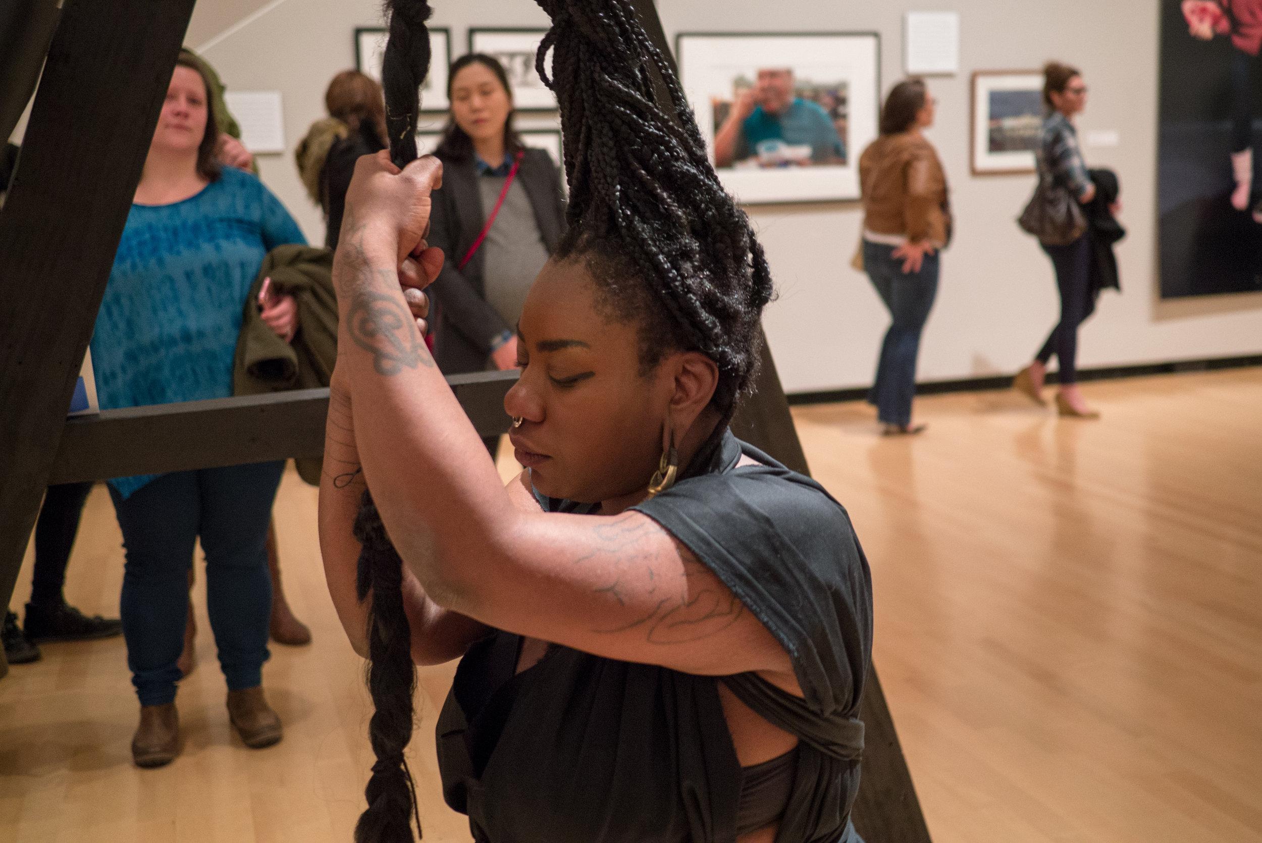 Powerful black woman holding braid in art performance
