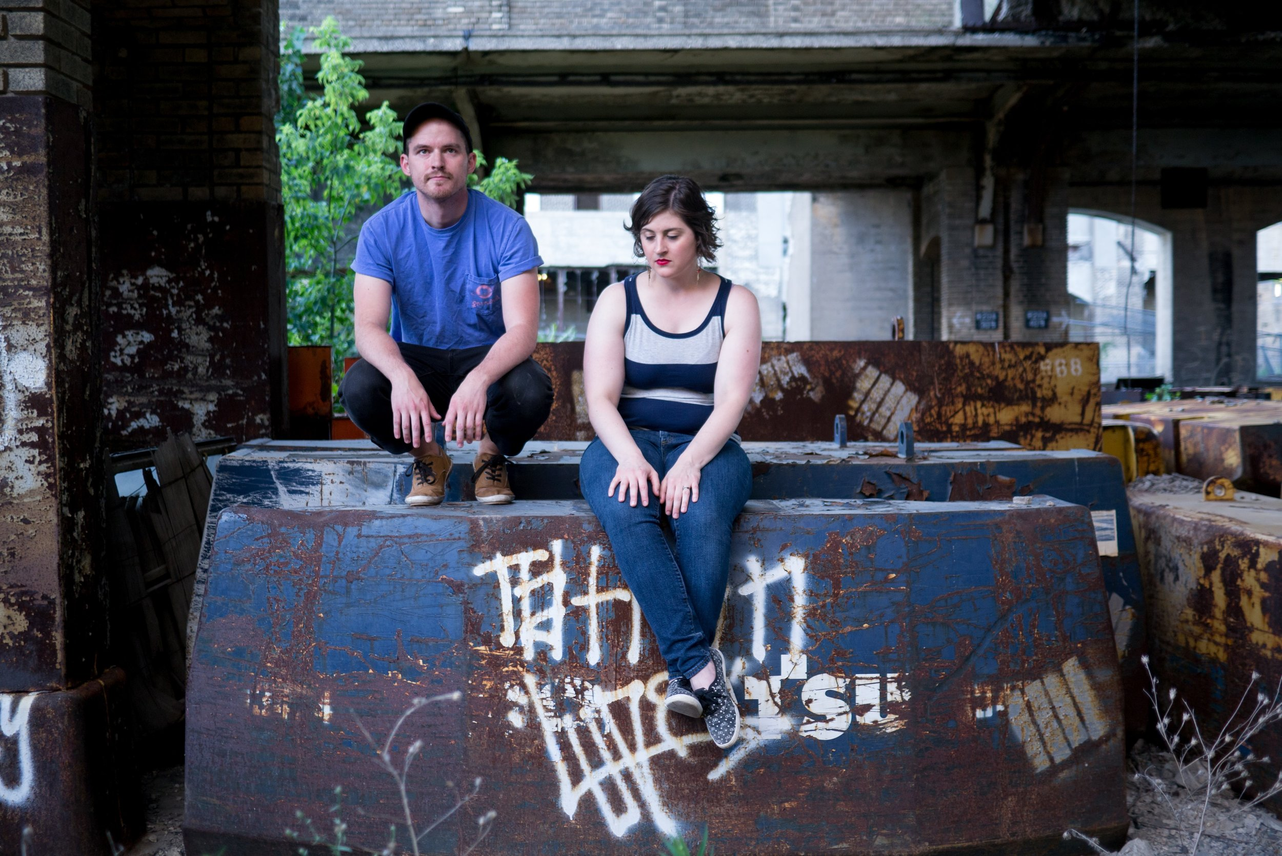 man and a woman sitting in an abandoned building