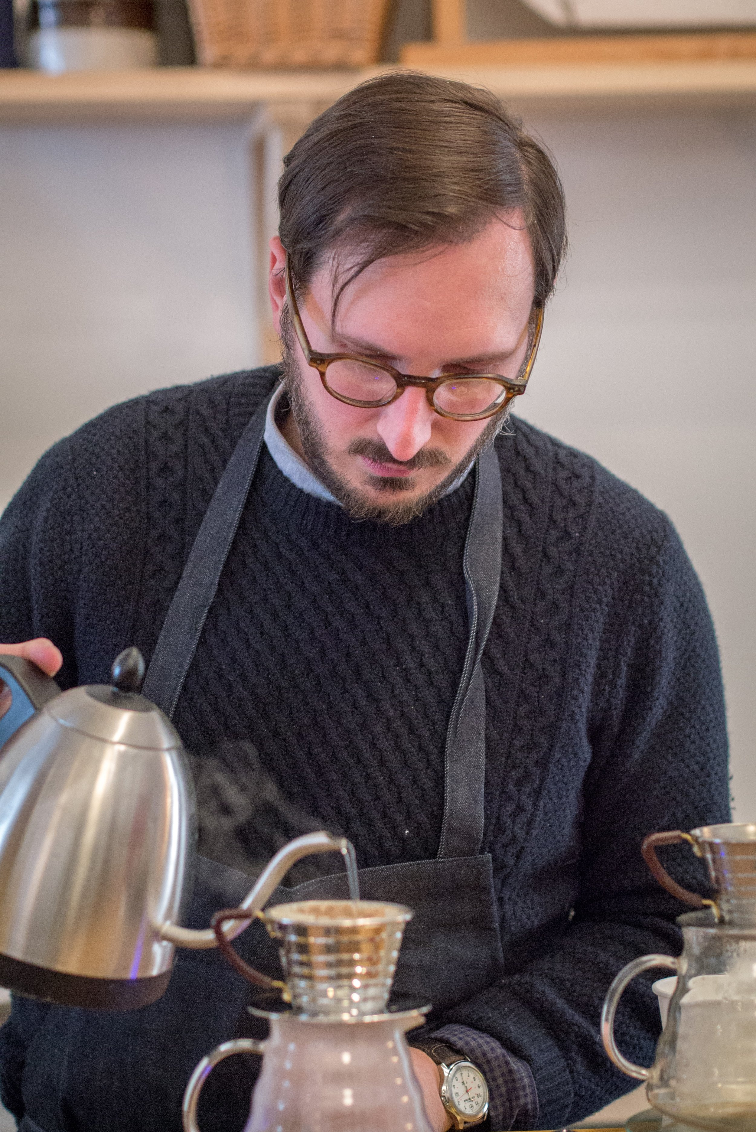 man preparing a pour over coffee with a tea kettle