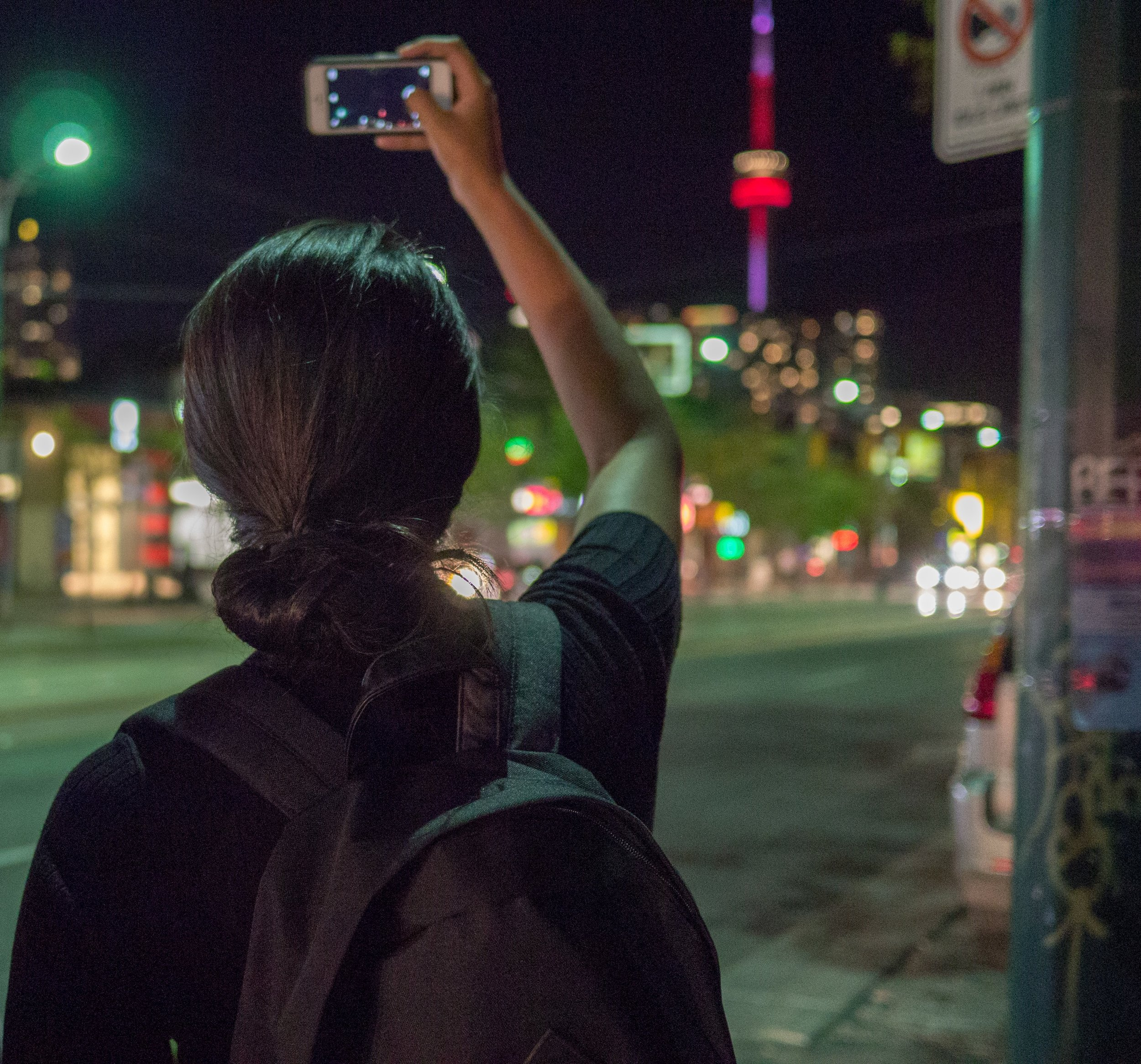 Woman taking photo of CN Tower in Toronto, ON