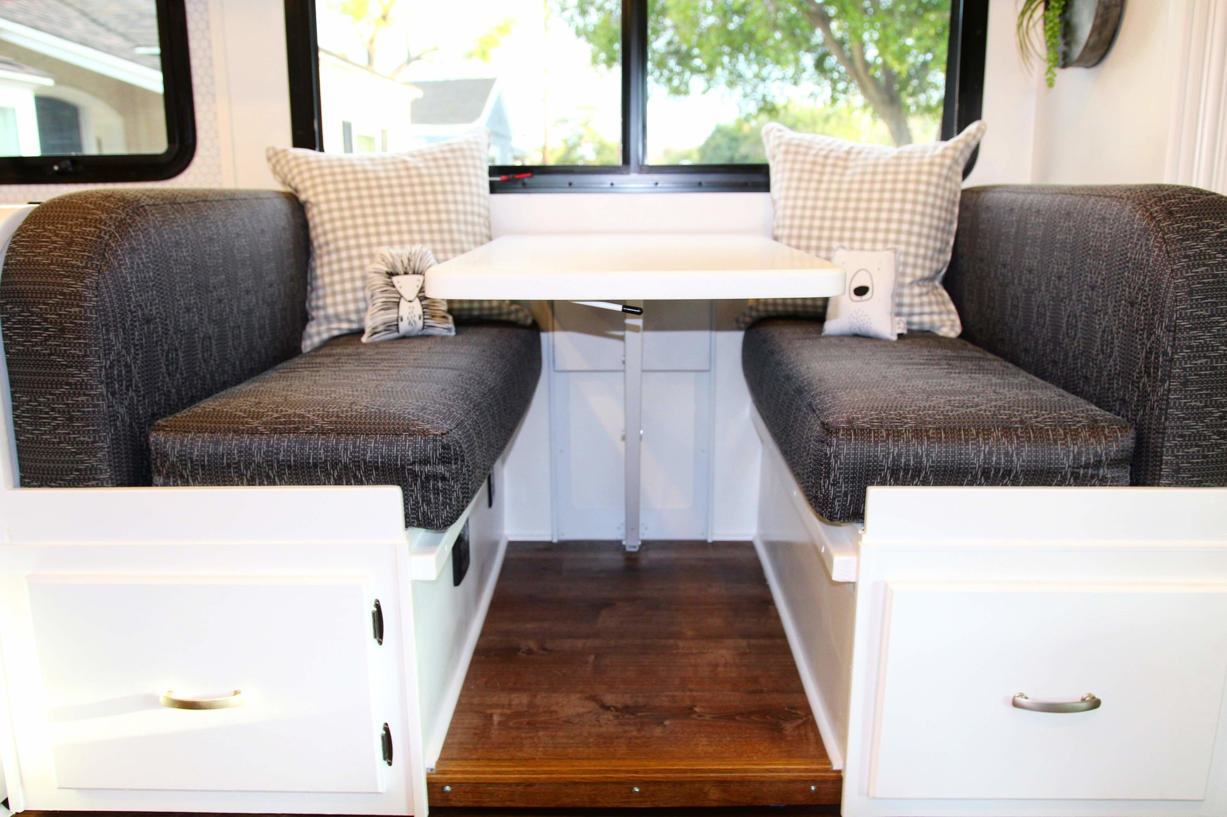 There was not one space not touched on their Class C. The dinette above has the cushions reinforced to be stronger bc there were plans to put car seats on them during their journey. Karlee and I went to Los Angeles to pick out fabric. I was so excited about this one. The design is very subtle but close up, it's beautiful! The table was custom to make the rest of the countertops in the RV. Below the cushions, Joe created draws to make this space more functional