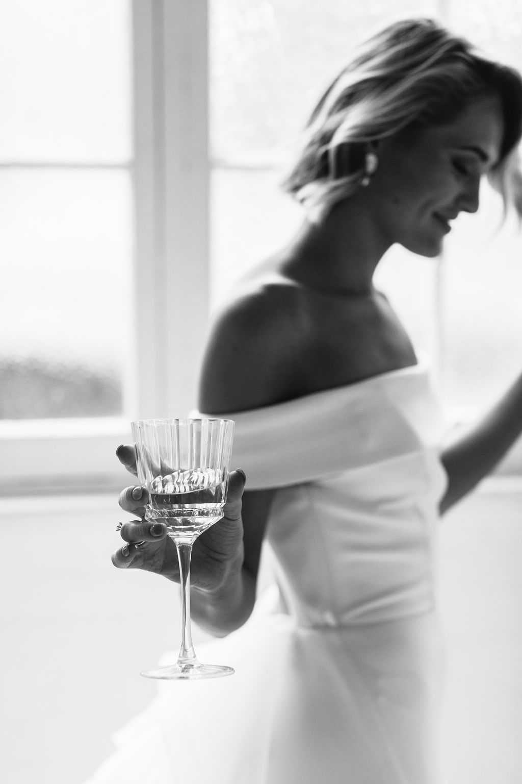 Black and white only bride dancing with champagne wearing gold pearl drop earrings with natural wavy bridal updo in afternoon wedding for Amelie George Jewellery Campaign