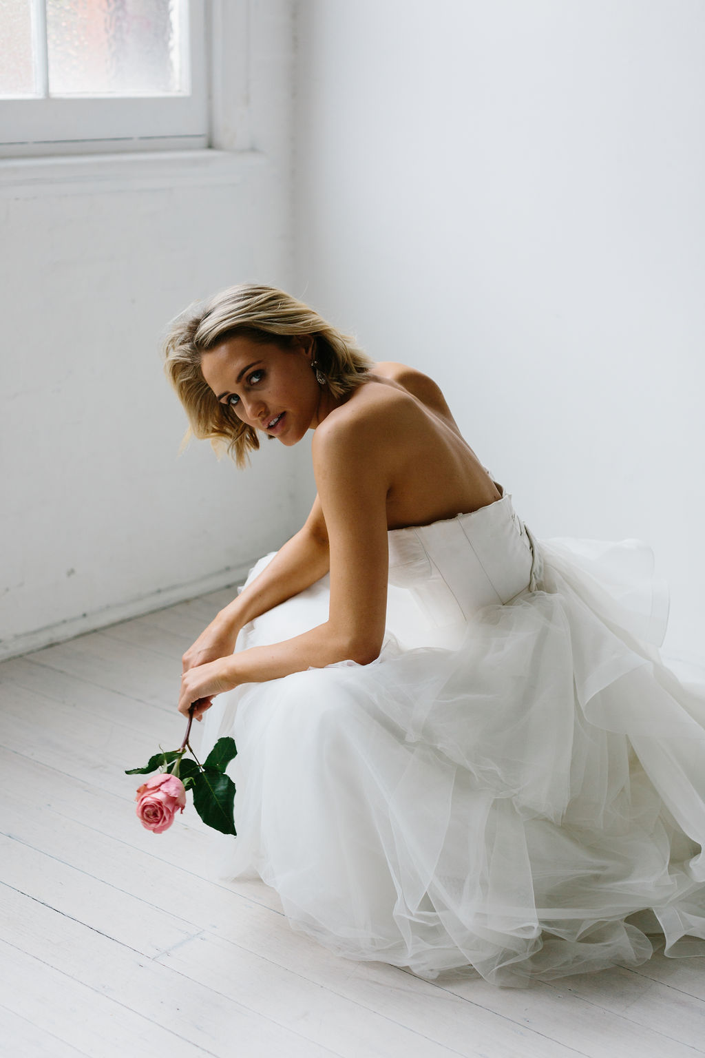 Bride in white room with single pink rose bouquet wearing minimalist modern wedding earrings and hairout with natural makeup for Amelie George Campaign