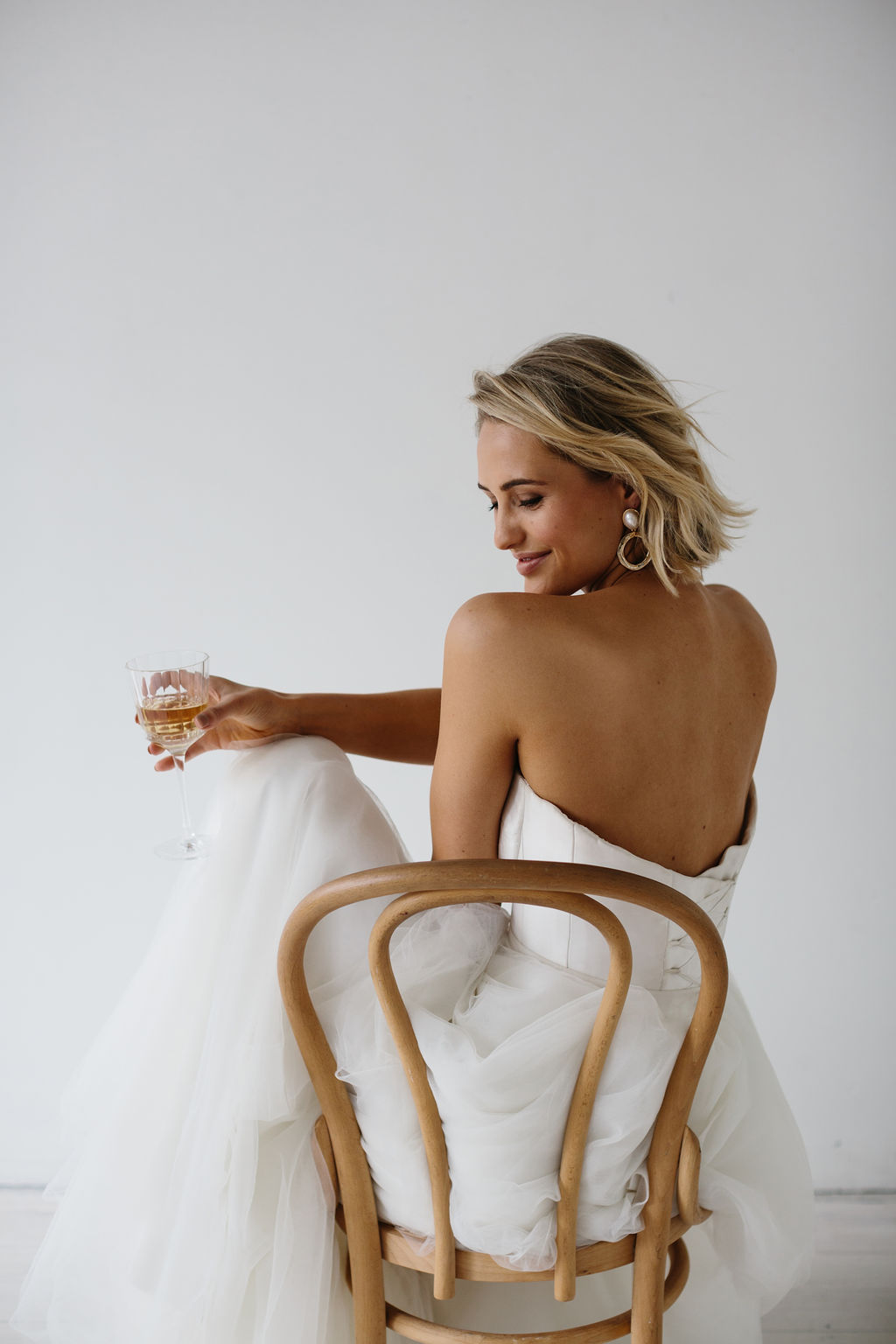 Backless Wedding Dress on bride in chair drinking champagne before wedding in large modern gold pearl earrings for Amelie George Campaign