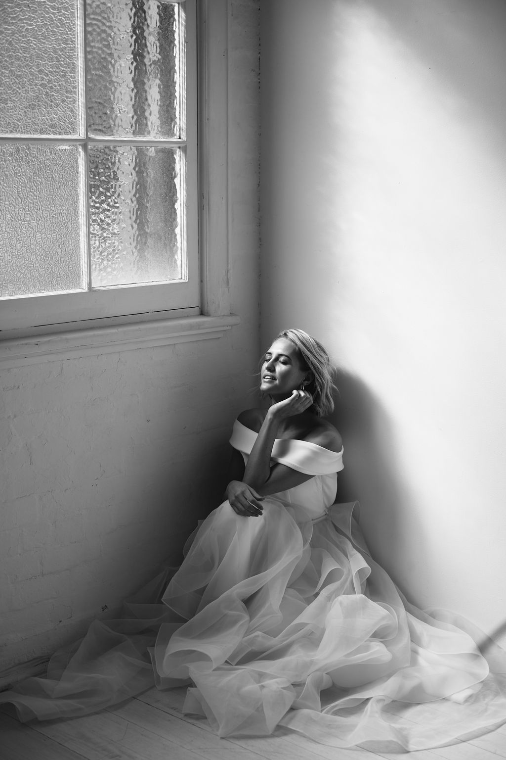 Black & white bride in corner wearing offshoulder dress and large tulle skirt using shadows for light in fashion photography for Amelie George Campaign