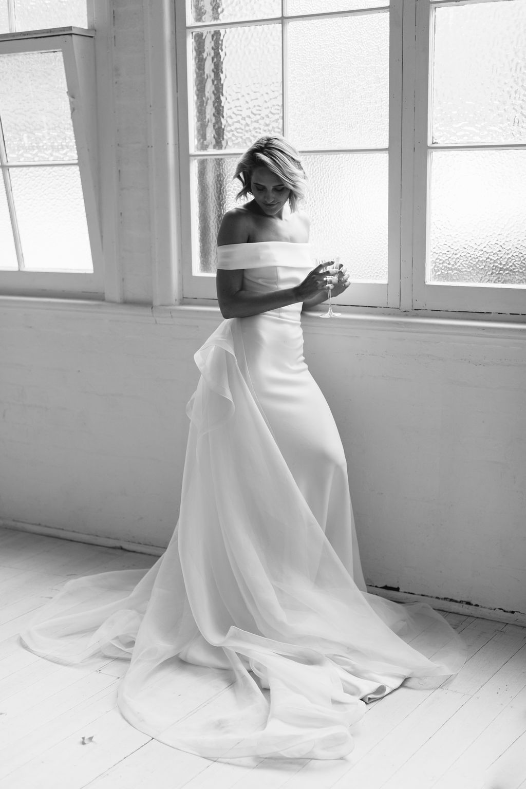 Perfect Bride before wedding drinking champagne in artdeco windows with large tulle train on floor for Amelie George Jewellery Campaign