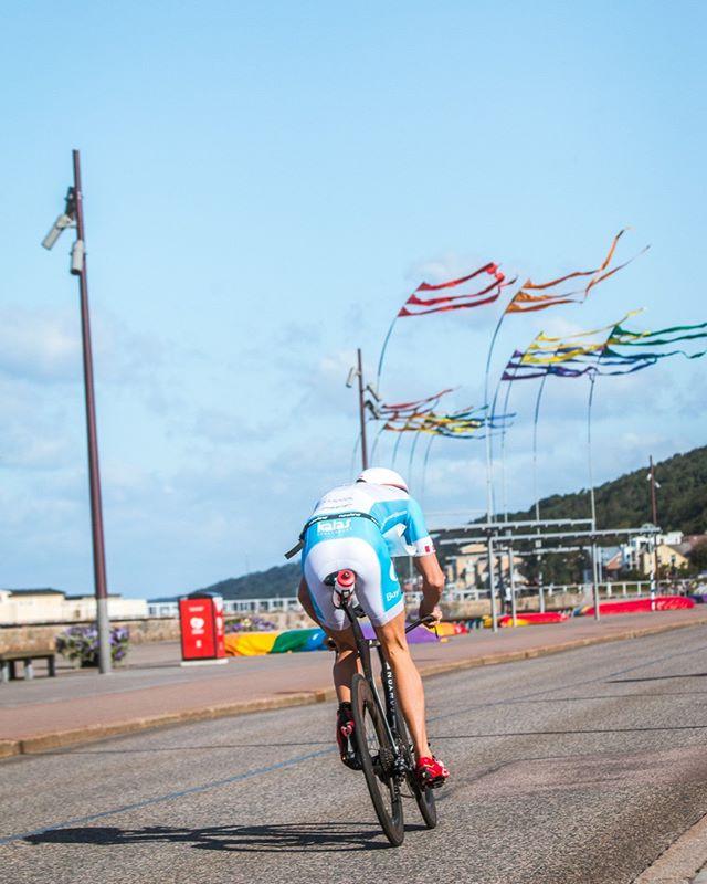Dagens tips inför Kalmar Ironman - Hantera vinden  Cyklingen under Kalmar Ironman är platt. På Öland är det superplatt och på fastlandet är det platt. Däremot är det många gånger inte lätt. Vinden kan göra cyklingen rejält tuff.  Om det blåser finns det några viktiga saker att tänka på. Om det blåser hård vind från sidan kan man i vissa fall behöva resa sig upp lite och luta kroppen mot vinden. Det gäller dock mest om flaggorna står som på bilden. Är det lättare sidvind och framförallt jämn vind är det bäst att göra sig låg och aerodynamisk. Det sparar absolut mest kraft och en låg position påverkas mindre av vinden. Skjut fram hakan mot händerna när du sitter i aeropositionen. Då blir du låg och aerodynamisk.  Är det motvind gör du likadant som vid sidvind. Gör dig liten mot vinden. Skjut fram hakan mot händerna och var kall. Bli inte stressad av att hastigheten är låg. Följ den tävlingsbelastning som du har bestämt dig för att hålla oavsett om den är baserad på watt (effekt) eller känsla. Låt det gå långsamt när det är tufft. Låt det sedan gå snabbt när det är lätt.  I medvind kan du passa på att sträcka mer på dig lite mer igen och passa på att ställa dig upp när du ökar farten efter kurvor eller hinder.  Jag har skrivit ett blogginlägg om cyklingen i Kalmar. Läs det och ta med dig några tips 🙂 Länk i bion!
