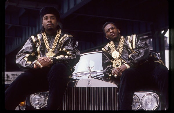 """Eric B. and Rakim in a behind-the-scenes shot from their music video for """"Follow the Leader,"""" in the late '80s, wearing logo'd designs by Dapper Dan."""