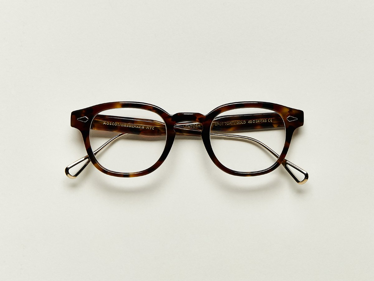 "MOSCOT - Lemtosh-TT SE Opticals  £310  COLOUR Tortoise/ Gold  SIZE 46  When Hyman arrived on Ellis Island 119 years ago, he heard, ""What is your name, where are you from?"" shouted from a distance. Although the ground was not paved in gold as promised, we wanted to honor his ambitious thinking by launching a Special Edition of the treasured LEMTOSH.  Handcrafted using a combination of metal and Italian acetate featuring unique patterns distinctive to each frame  Features diamond rivets  Comfortable key hole nose bridge  Includes acetate nose pads  7-Barrel hinge  MOSCOT temple engravings  Exclusive gold titanium temple tips"