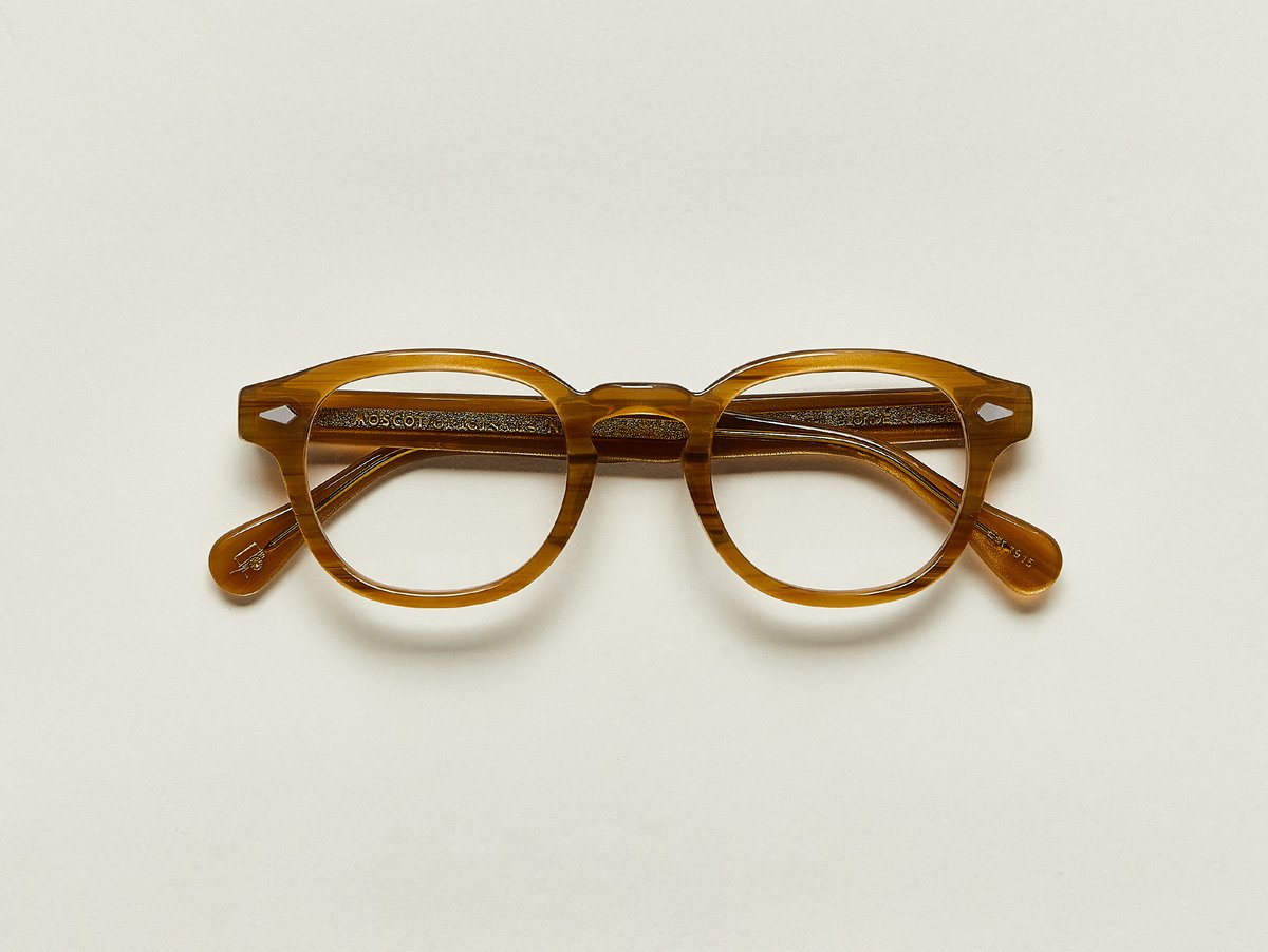 MOSCOT - Lemtosh Opticals  £245  COLOUR Blonde  SIZE 44  This rounder number has served as the calling card for generations of creative, thoughtful, free-spirited intellectuals and artistes – from James Dean to Johnny Depp.  Handcrafted using Italian acetate featuring unique patterns distinctive to each frame  Features diamond rivets  Comfortable key hole nose bridge  Includes acetate nose pads  7-Barrel hinge  MOSCOT temple engravings  Signature acetate tips