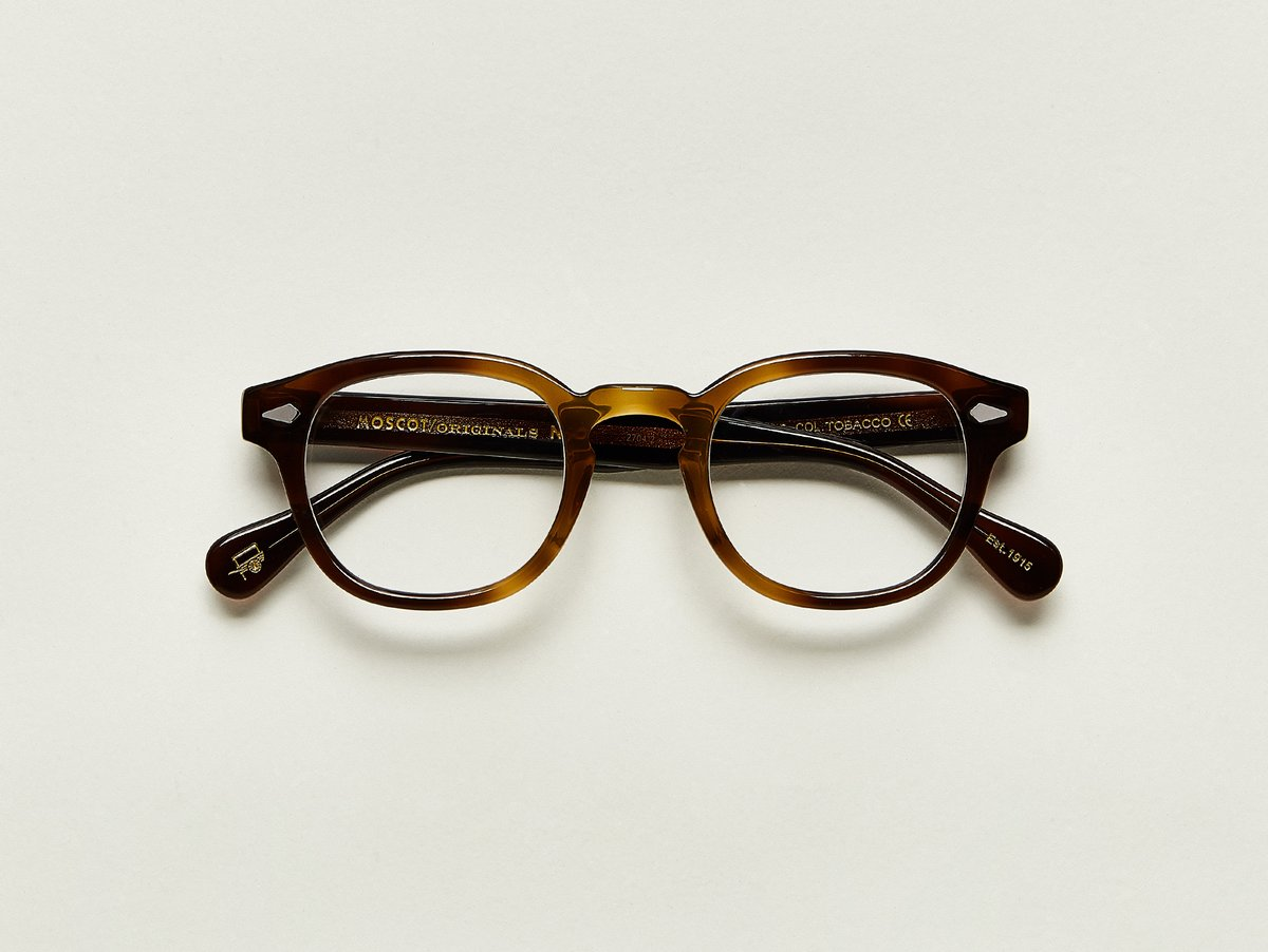MOSCOT - Lemtosh Opticals  £245  COLOUR Tobacco  SIZE 49  This rounder number has served as the calling card for generations of creative, thoughtful, free-spirited intellectuals and artistes – from James Dean to Johnny Depp.  Handcrafted using Italian acetate featuring unique patterns distinctive to each frame  Features diamond rivets  Comfortable key hole nose bridge  Includes acetate nose pads  7-Barrel hinge  MOSCOT temple engravings  Signature acetate tips