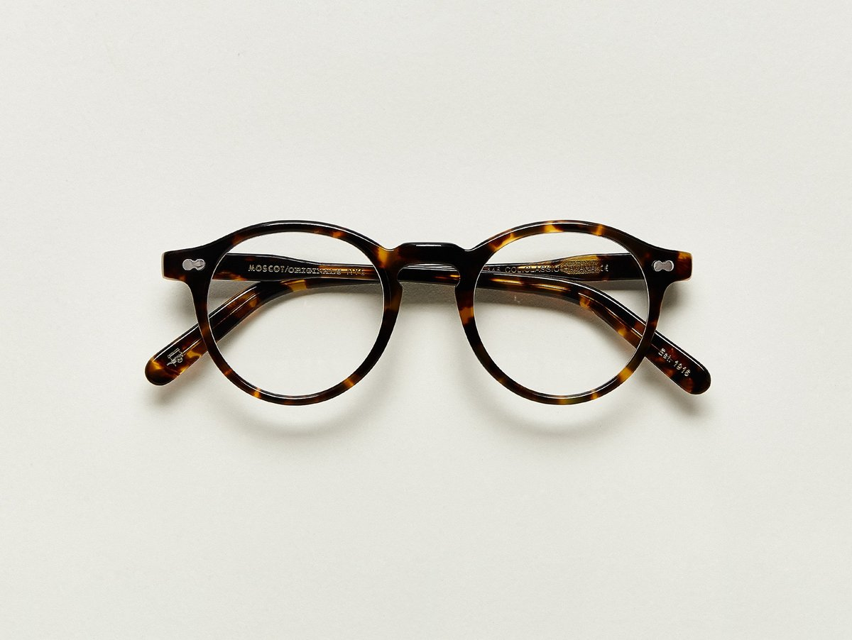 MOSCOT - Militzen Opticals  £245  COLOUR Classic Havana  SIZE 49  The round, full-vue MILTZEN, first introduced in the 1930s, is eponymously named for our Uncle Heshy, who inexplicably everyone called Uncle Miltzen. And it stuck. So there you go, world... The MILTZEN.  Handcrafted using Italian acetate  Features adjoined dot rivets  Comfortable key hole nose bridge  Includes acetate nose pads  3-Barrel hinge  MOSCOT temple engravings