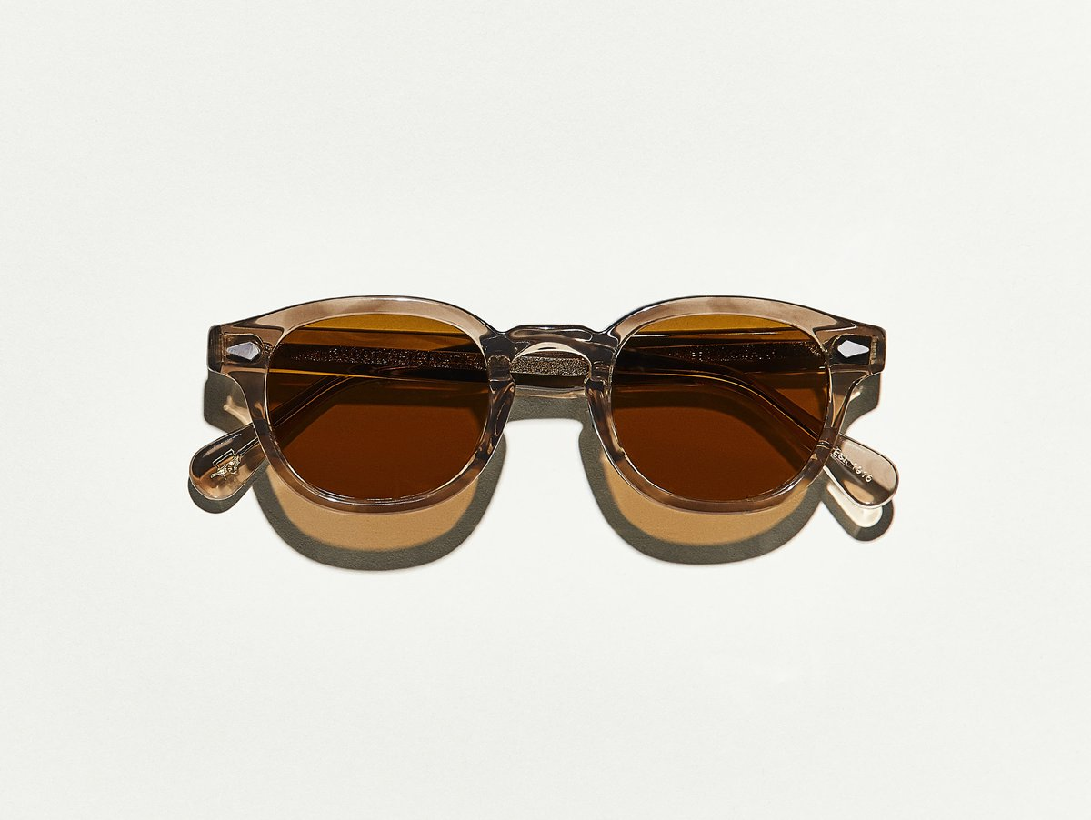 MOSCOT - Lemtosh Sunglasses  £265  COLOUR Brown Ash  SIZE 46  This rounder number has served as the calling card for generations of creative, thoughtful, free-spirited intellectuals and artistes – from James Dean to Johnny Depp.  Handcrafted using Italian acetate featuring unique patterns distinctive to each frame  Features diamond rivets  Features real glass lenses in Cosmitan Brown