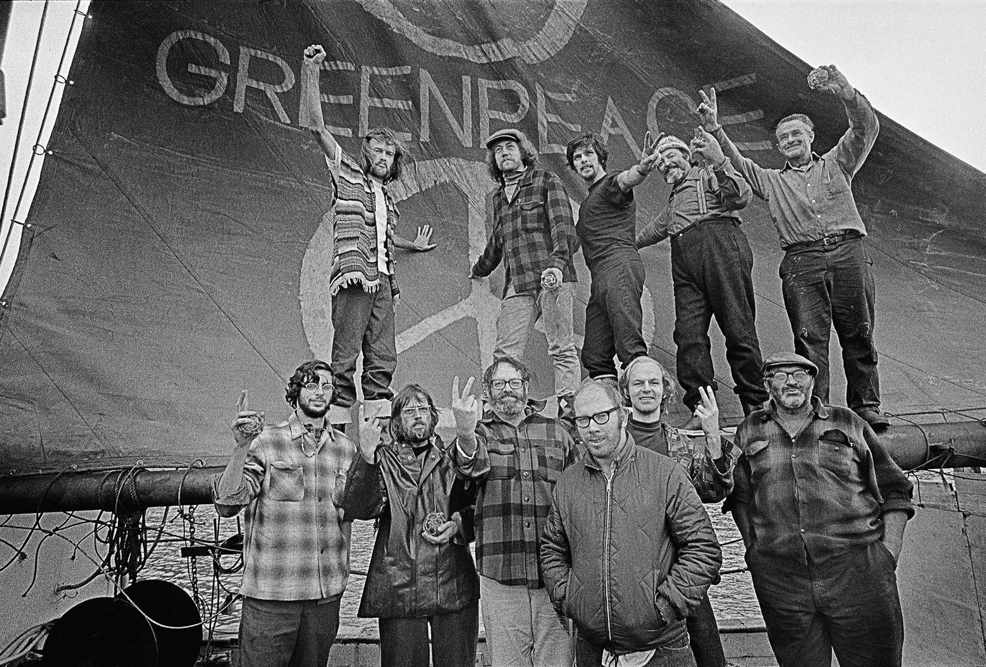 "The crew of the Phyllis Cormack (also called ""Greenpeace"") on-board the ship. Clockwise from top left: Bob Hunter, Patrick Moore, Bob Cummings, Ben Metcalfe, Dave Birmingham, John Cormack, Bill Darnell (who coined term 'Greenpeace'), Terry Simmons, Jim Bohlen, Lyle Thurston and Richard Fineberg. Photo by Robert Keziere."
