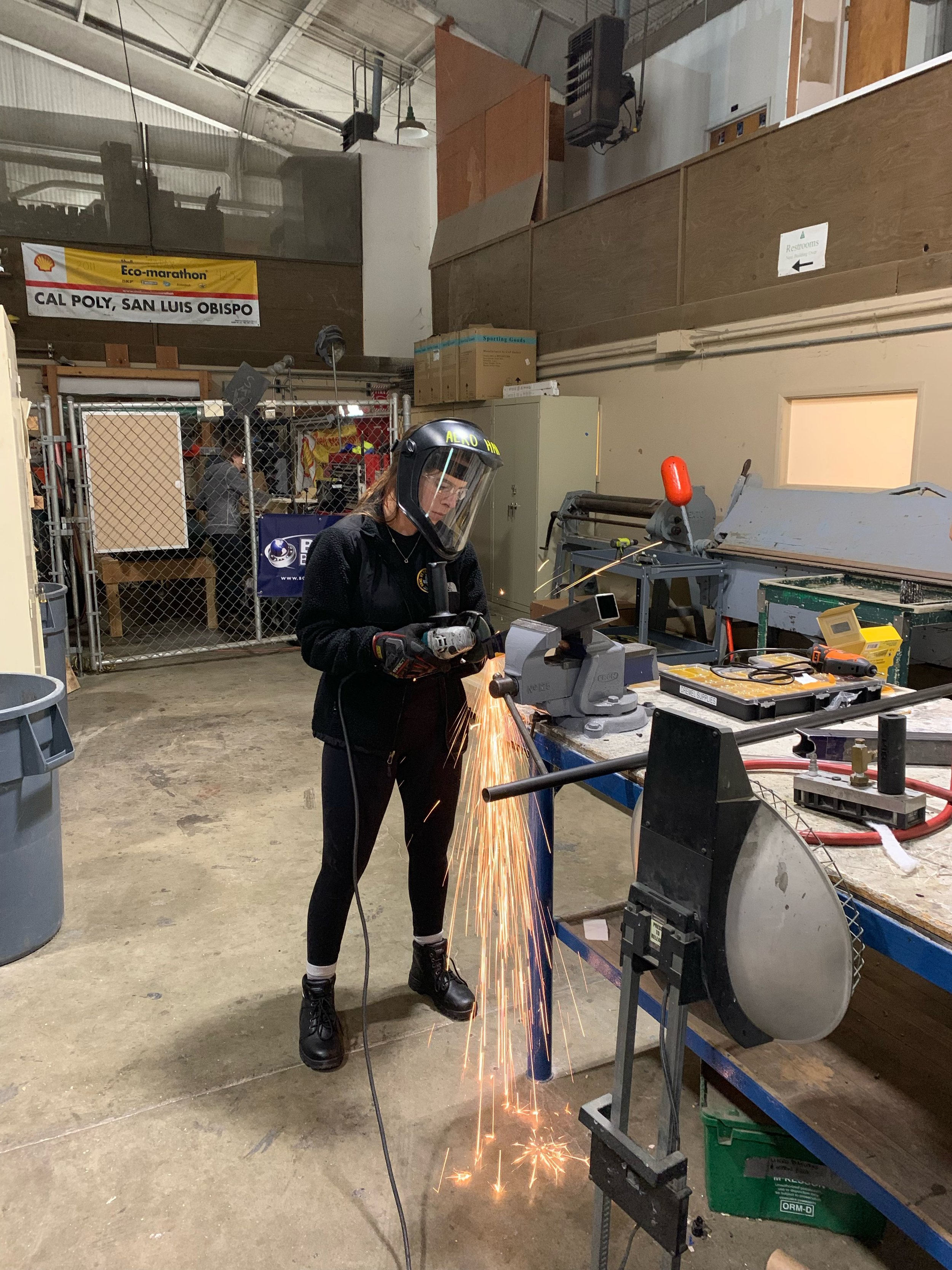 Frame Work - Keyanna Henderson uses an angle grinder to miter a steel tube for our frame jig.