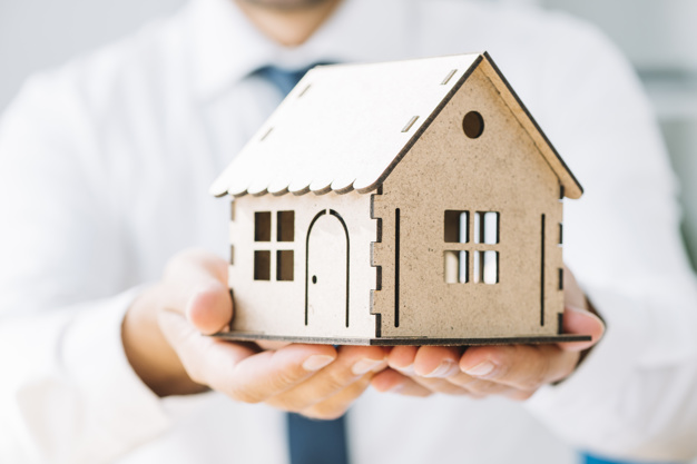 close-up-real-estate-agent-with-toy-house_23-2147797627.jpg