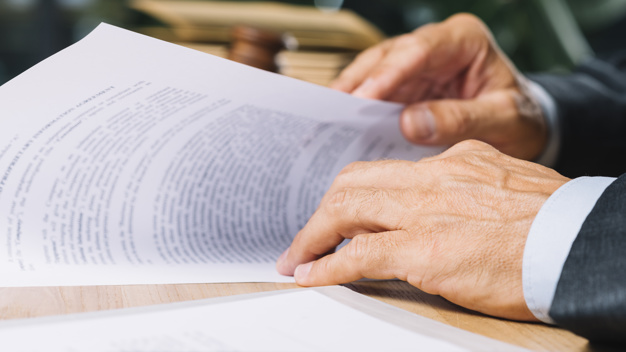 male-lawyer-s-hand-holding-document-desk-courtroom_23-2147898384 (1).jpg