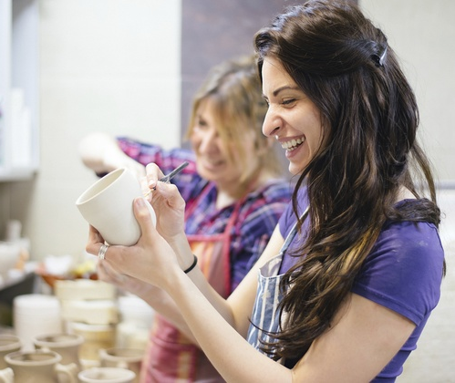 two women painting ceramics.png