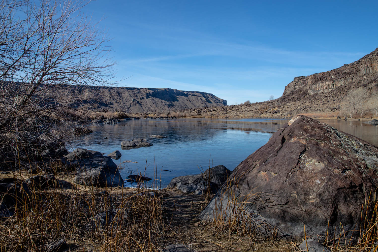 Halverson Lake in Melba Idaho with rocks all around and pretty dry scenery in the winter. Blue skies with wispy clouds.