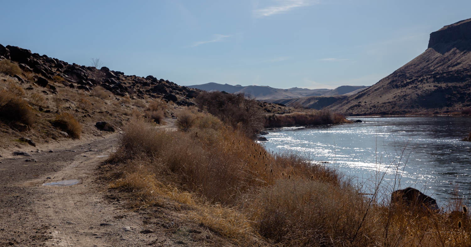 Hiking path along the Snake River in Idaho not he way to Halverson Lake. Pretty dry surroundings with rocks and mountain cliffs alongside the river. Icy puddles and wispy clouds in the sky.