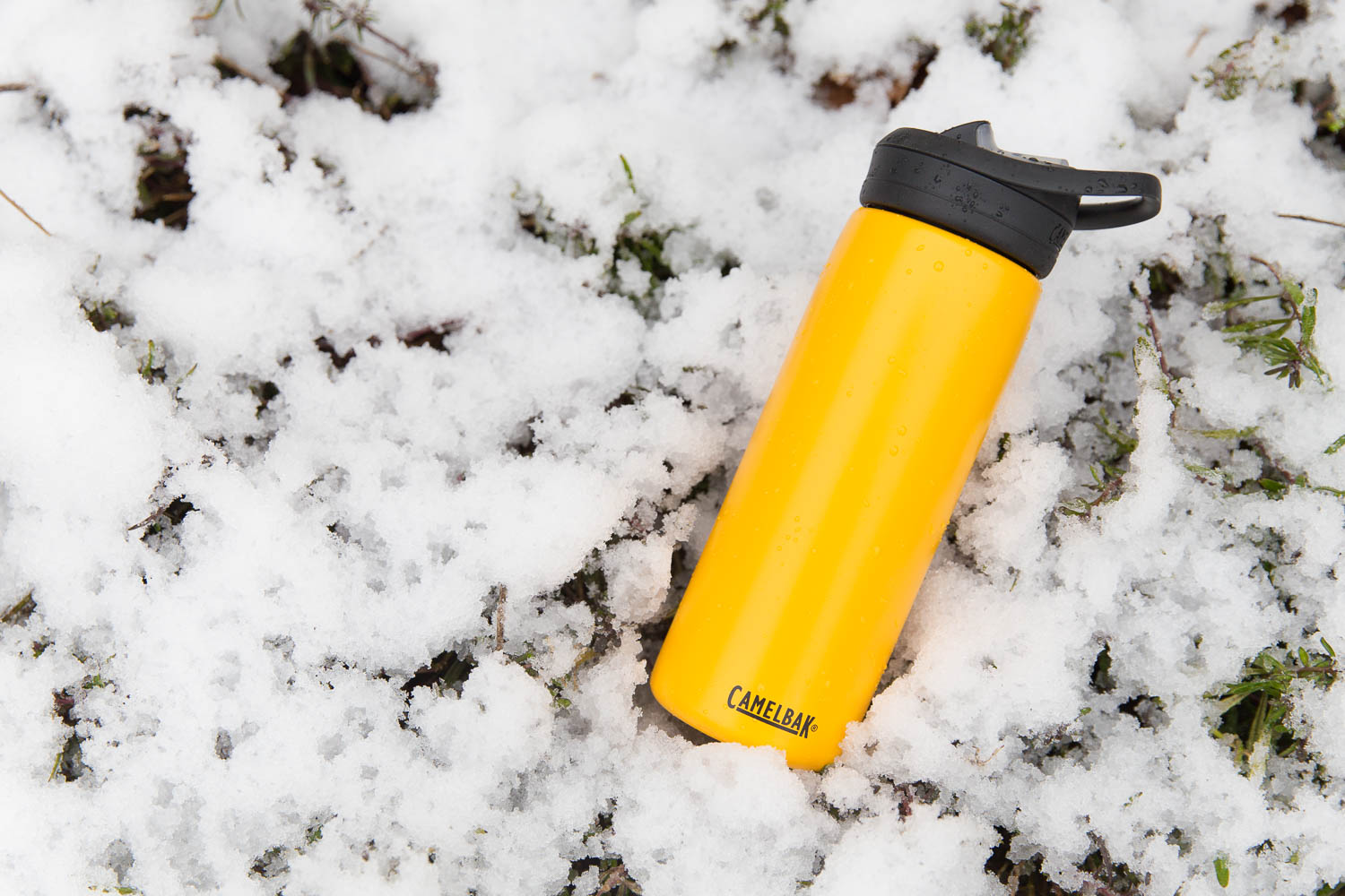 yellow camelbak insulated water bottle sitting in the snow