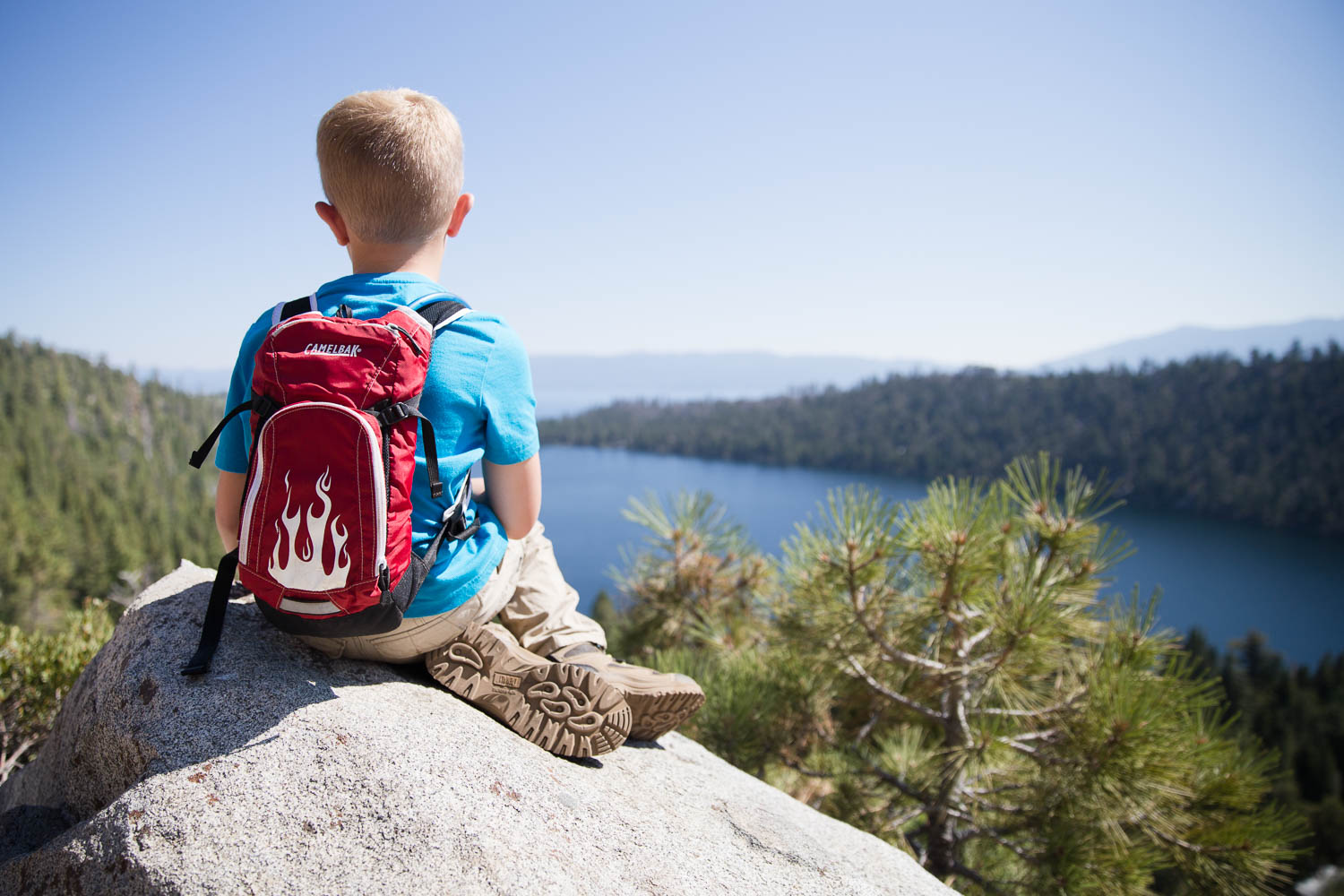 Young boy sitting on rock overlooking a lake by Lake Tahoe in California