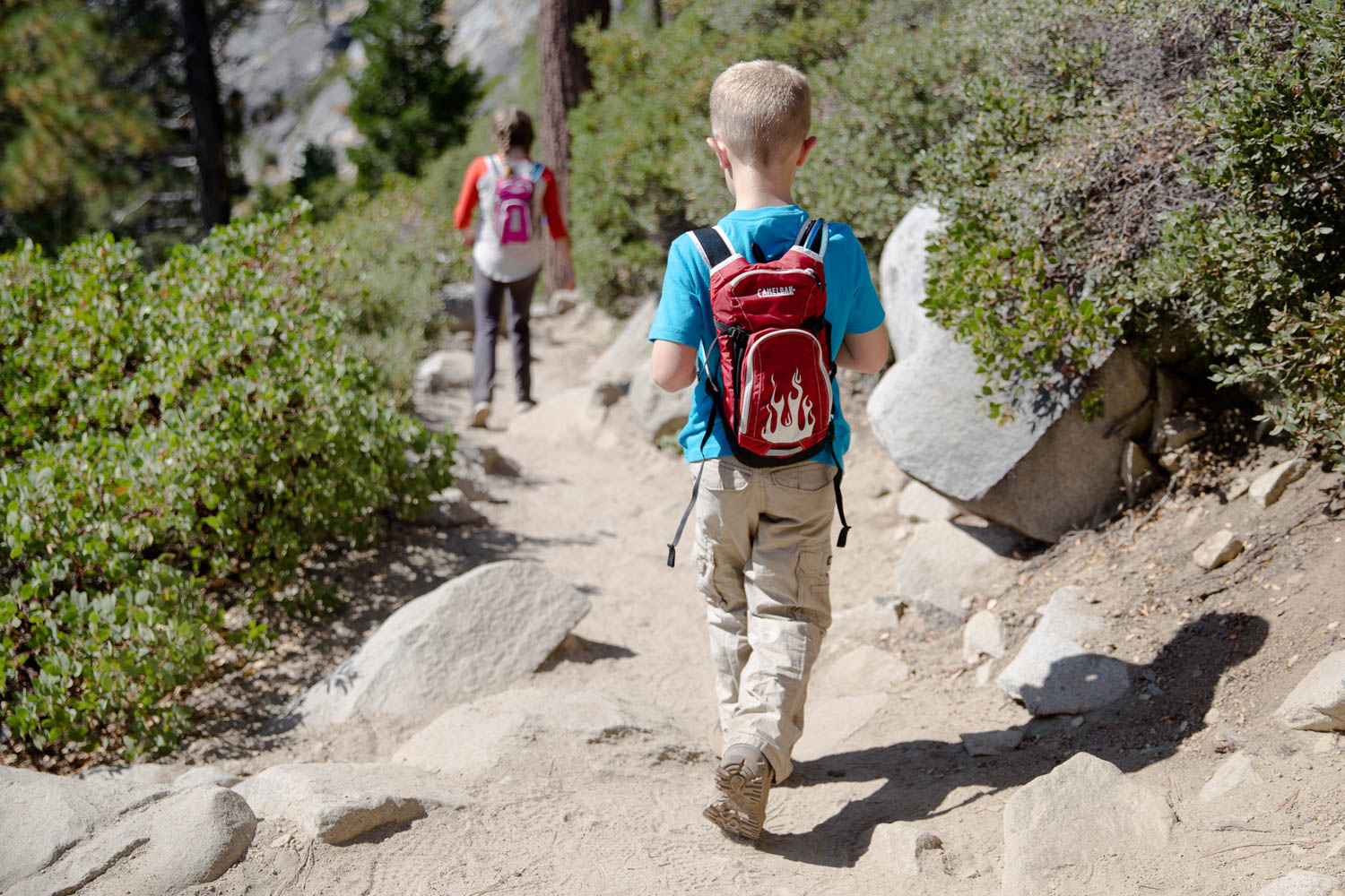Two young kids with hydration backpacks on a hike by Lake Tahoe