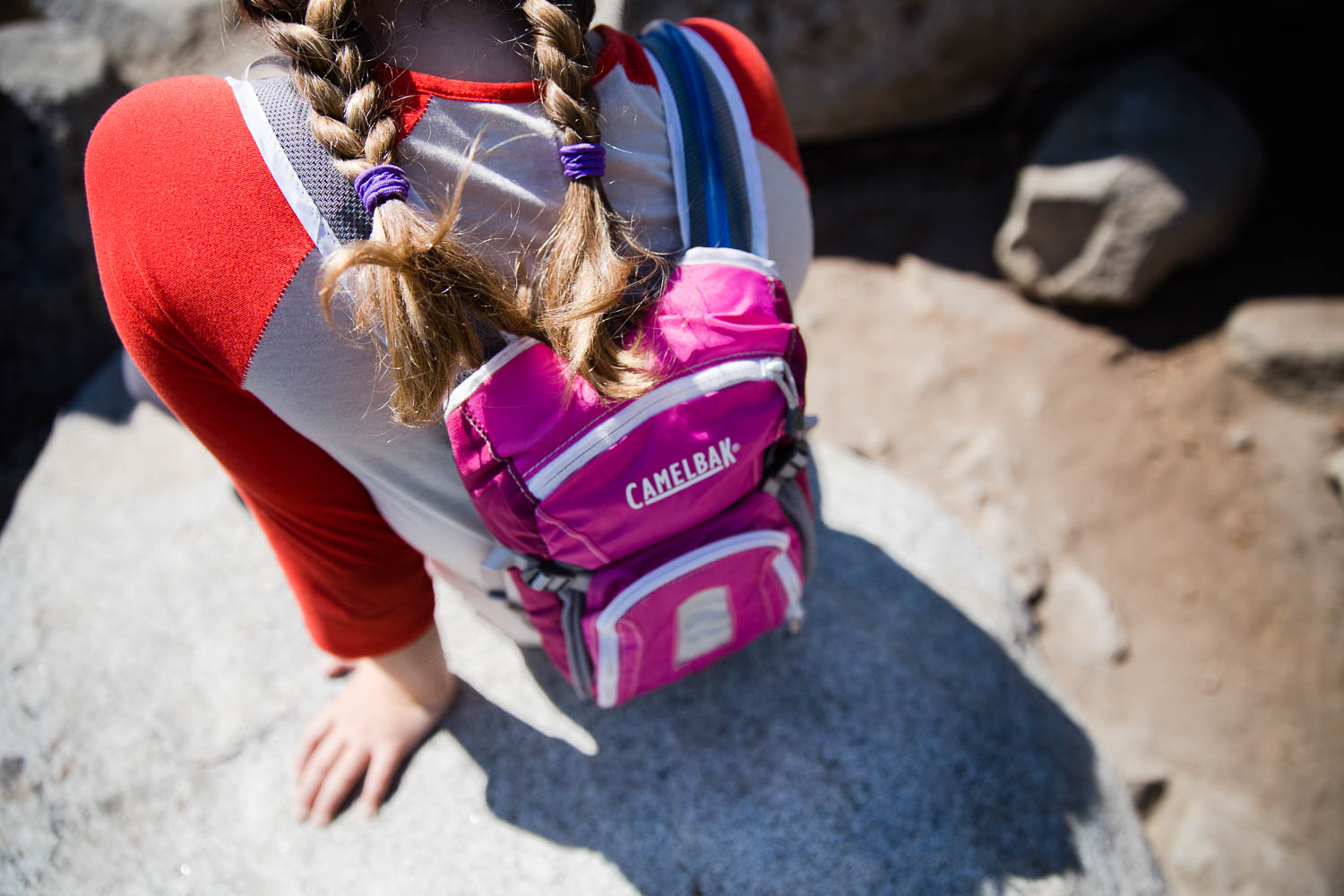 Young girl sitting on rock leaning back as she wears her Camelbak hydration backpack