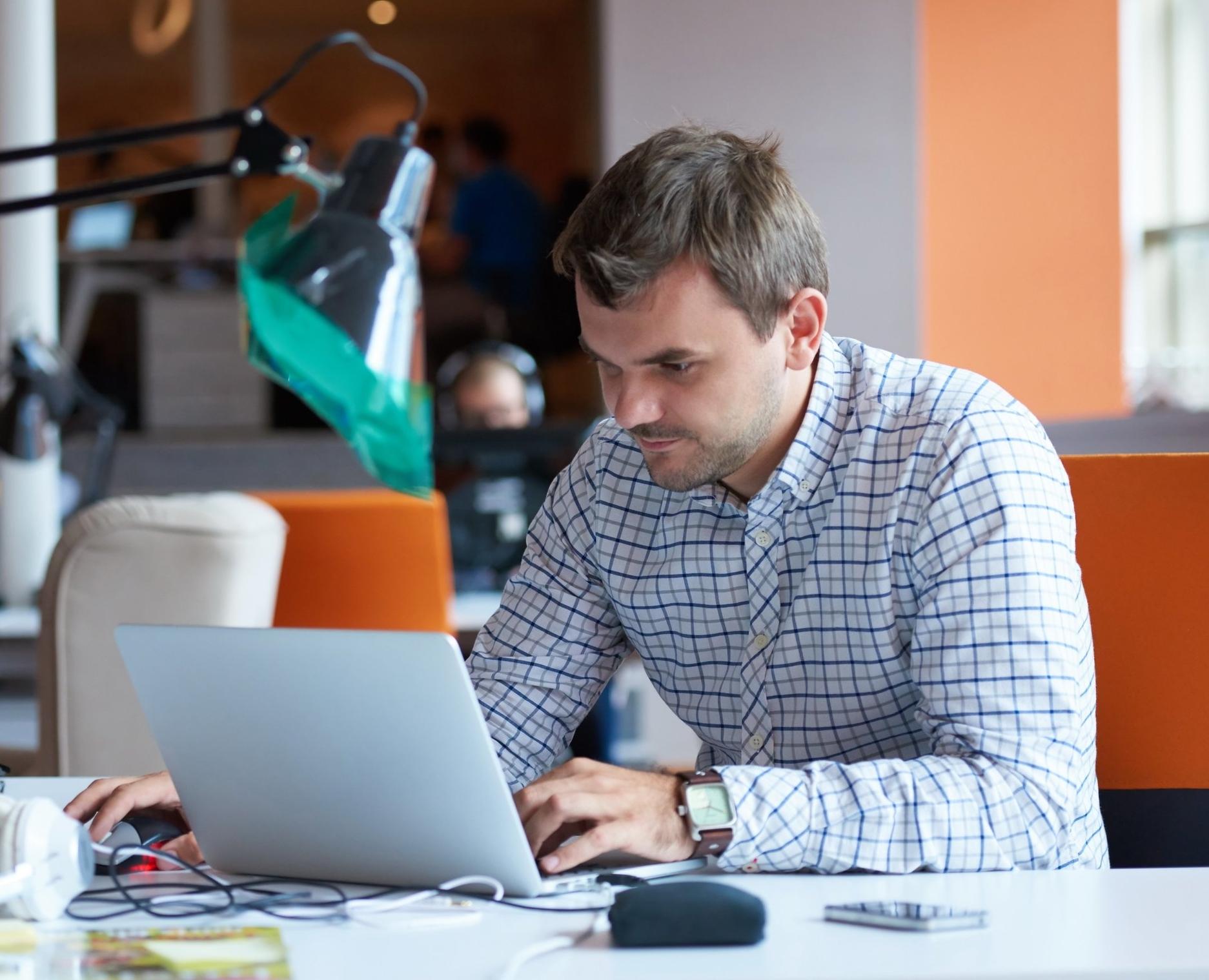 Man i skjorta med bärbar dator