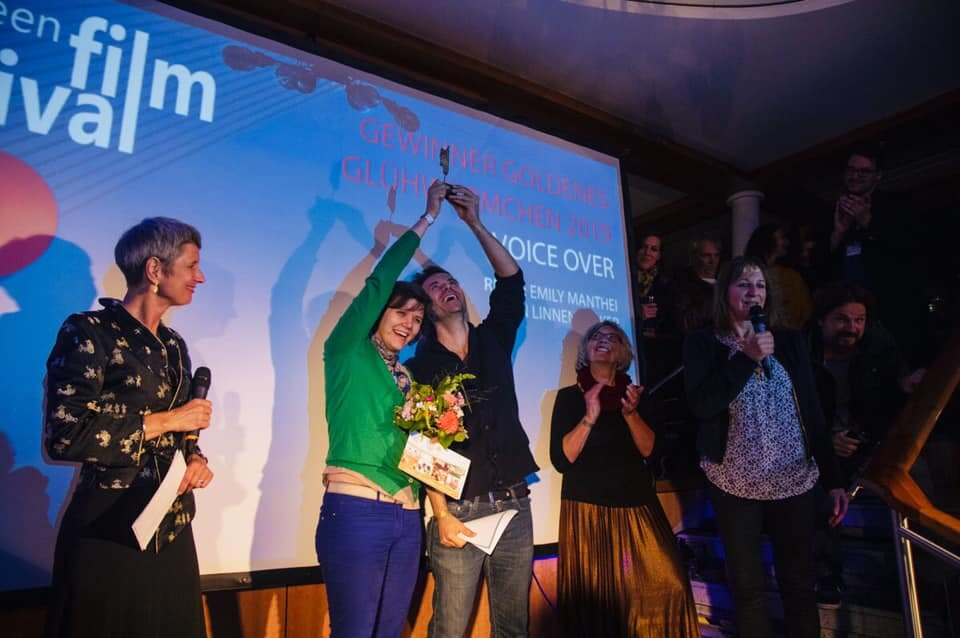 "11 September, 2019 : Voice Over wins ""Das Goldene Glühwurmchen"" at the Fünf Seen International Film Festival. Written and directed by Emily Manthei and Jörn Linnenbröker, ""Voice Over"" has competed in 15 festivals in 2019. Our ""Golden Firefly"" is from the voting audience award in Starnberg, Germany."