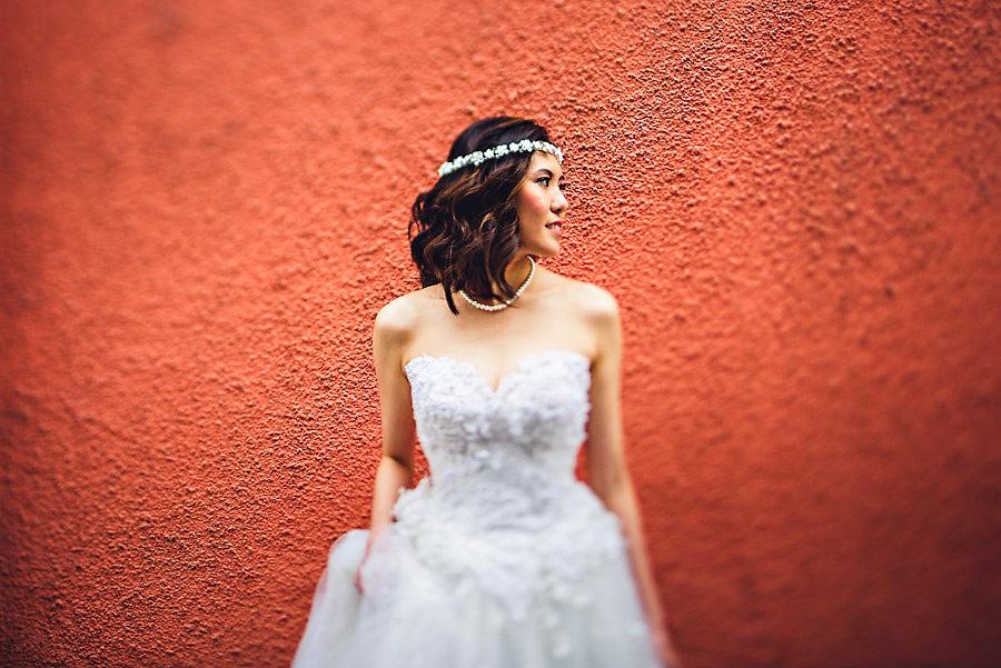 Portrett av bruden i Praha foran en rød vegg med tilt shift obj