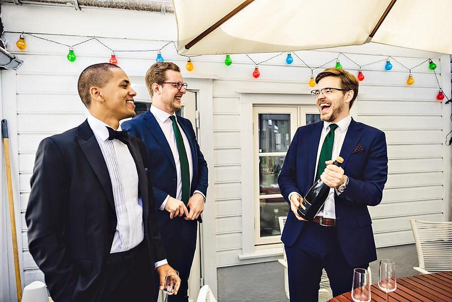 brudgom og forlovere koser seg med champagne før bryllup i stav