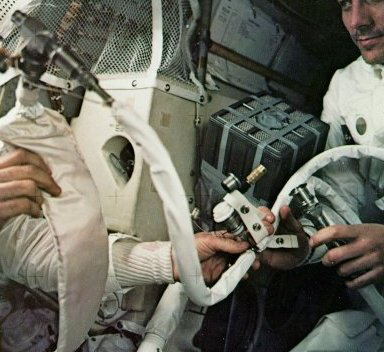 Swigert sitting next to a taped-over double canister and holding one end of a suit nozzle while Fred Haise used both his hands to manipulate the long hose. Underneath the canister is a 'mailbox' built of arched cardboard, which was covered by a plastic bag - CapCom Joe Kerwin led Astronaut Swigert, step by step, for an hour to build a contraption like the one the experts had constructed on Earth. It involved stripping the hose from a lunar suit and rigging the hose to the taped-over command module double canister, using the suit's fan to draw carbon dioxide from the cabin through the canister and expel it back into the lunar module as pure oxygen.