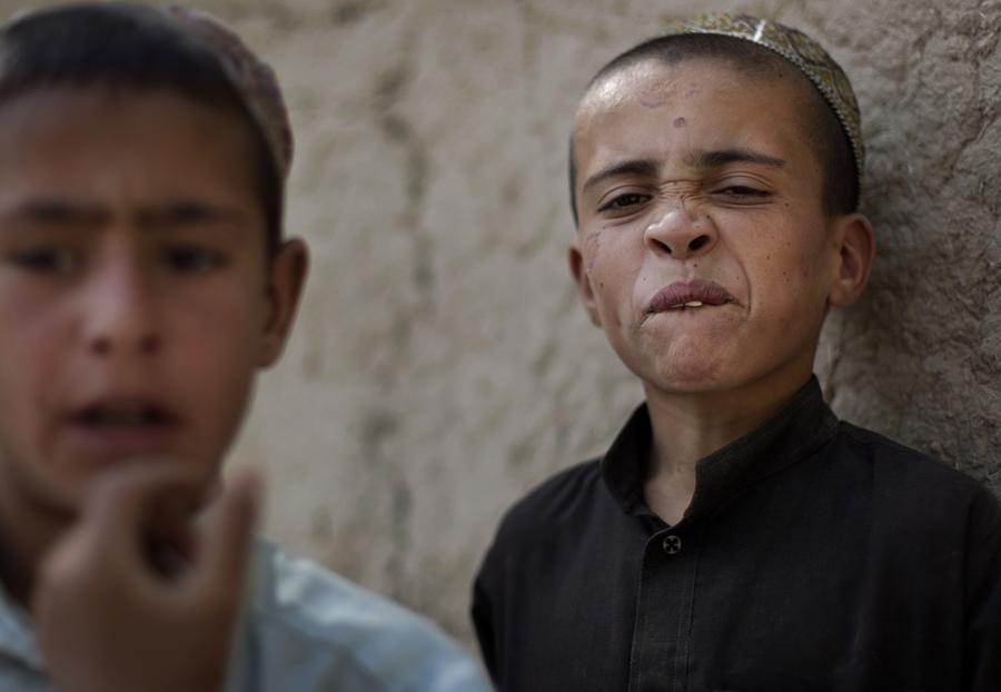 An Afghan boy makes a face as Canadian soldiers with the 1st Battalion, The Royal Canadian Regiment and Afghan Army soldiers patrol the village of Salavat in the Panjwayi district, June 1, 2010.
