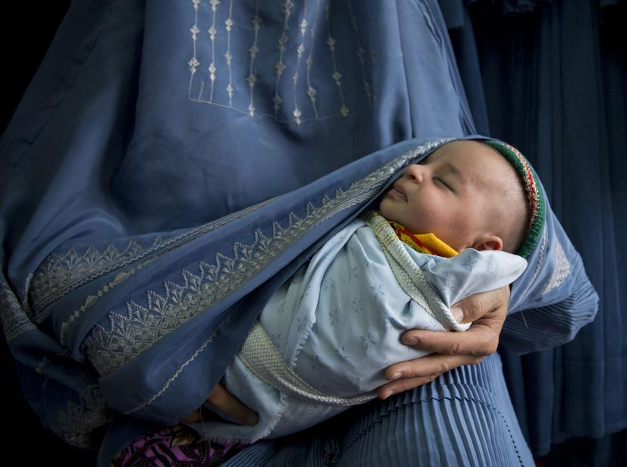 An Afghan woman holds her newly born baby wrapped in her burqa as she waits to get in line to try on a new burqa in a shop in the old town of Kabul, April 11, 2013.