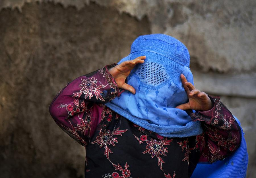 An Afghan girl tries to peer through the holes of her burqa as she plays with other children in the old town of Kabul, Afghanistan, April 7, 2013.